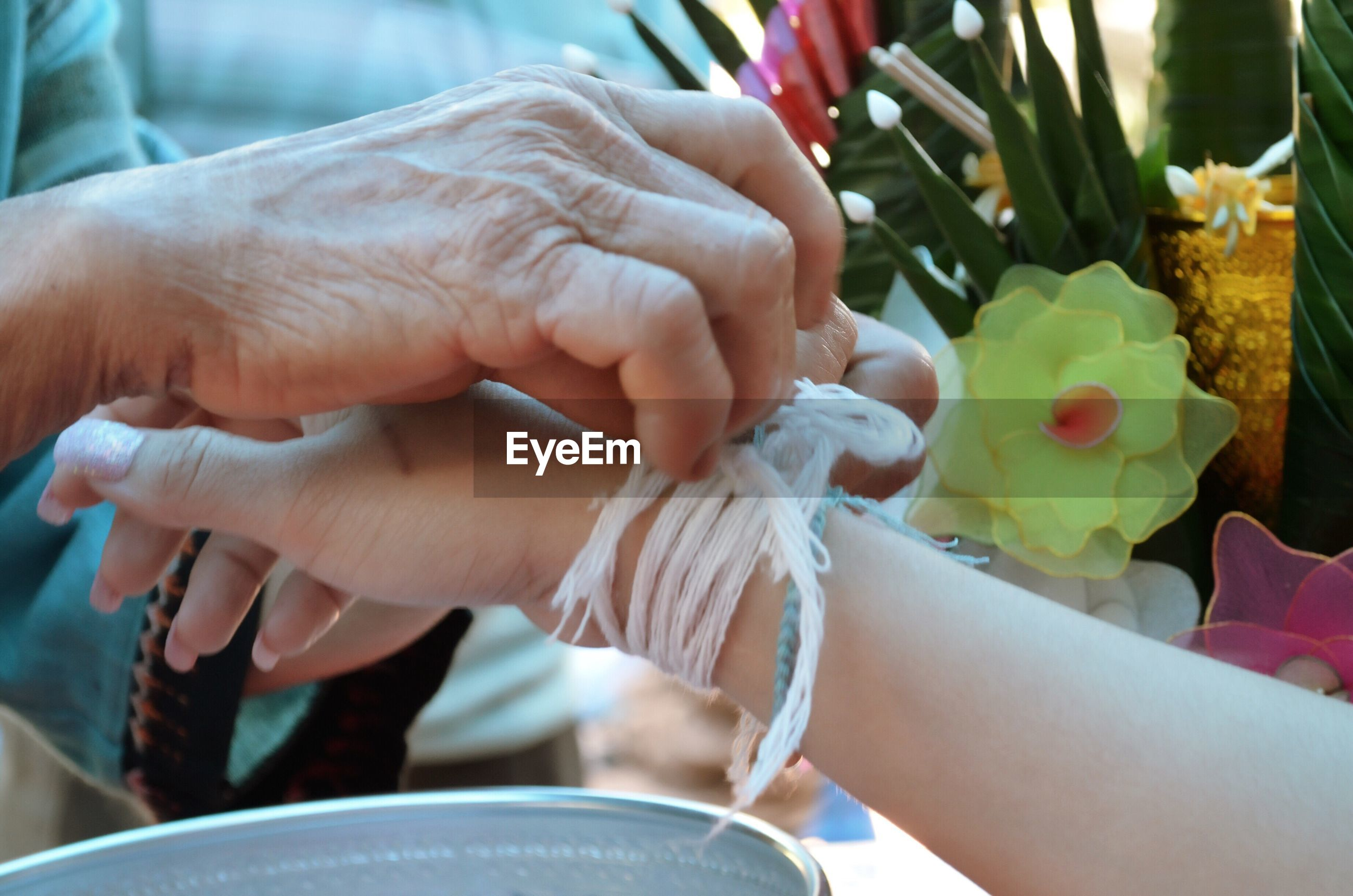 Cropped image of female tying string in woman hand