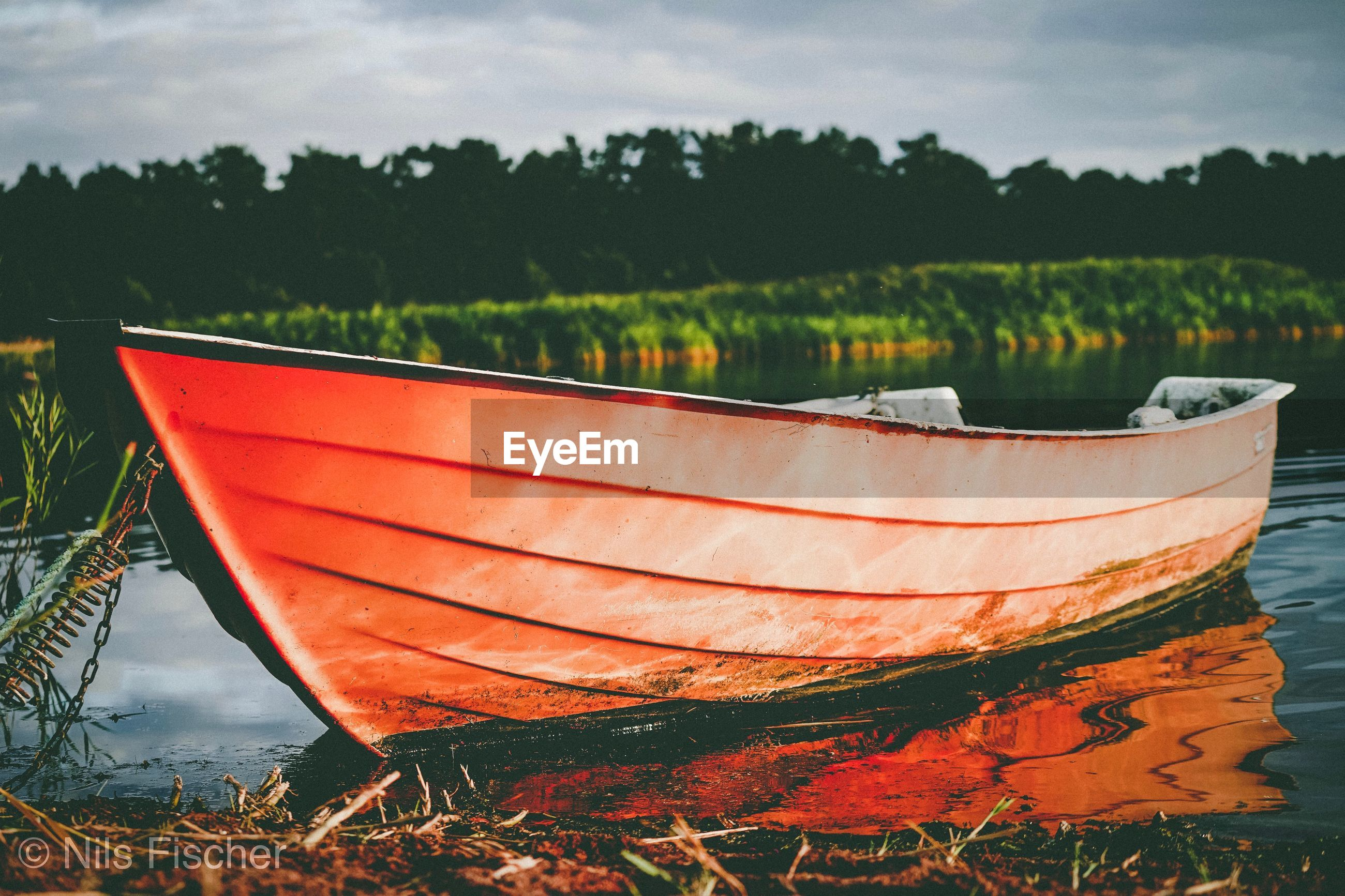 RED BOAT MOORED ON LAKE AGAINST SKY