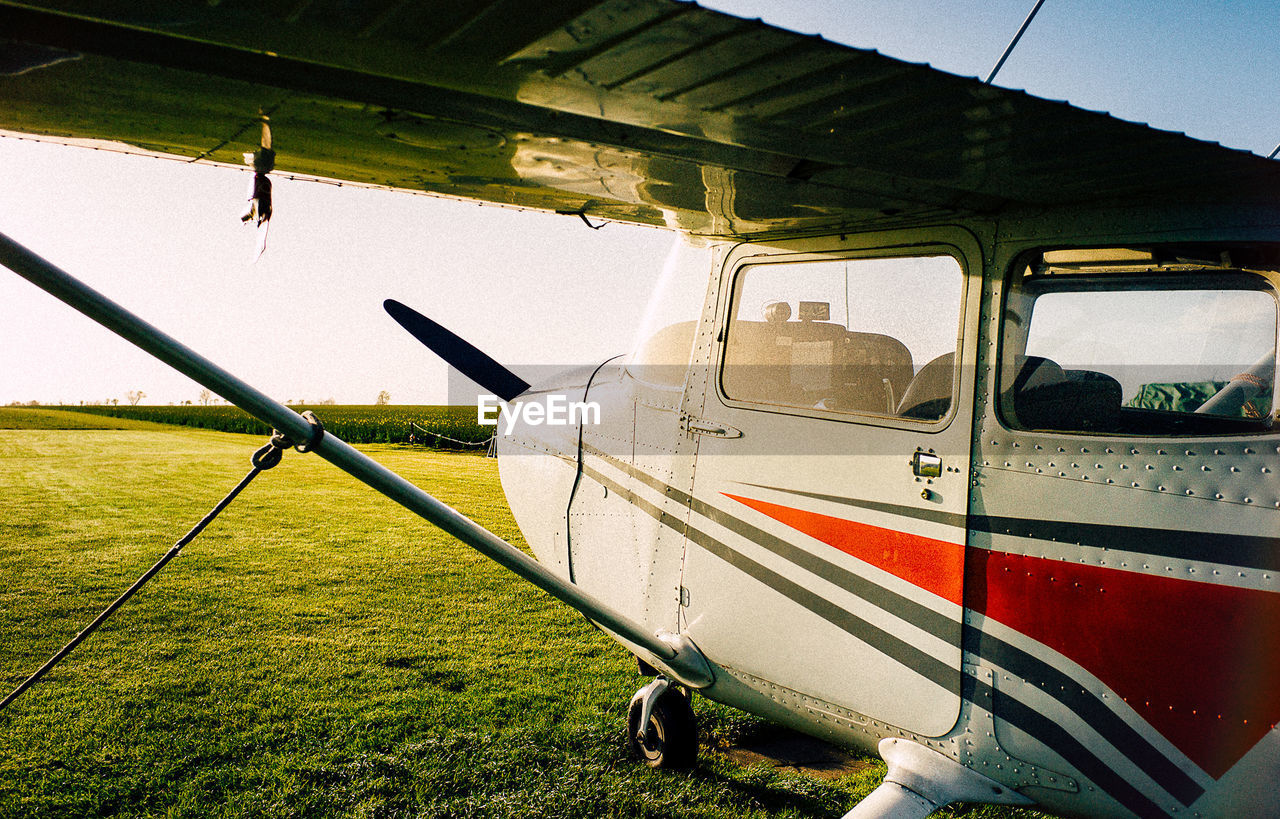 transportation, mode of transport, public transportation, grass, day, journey, land vehicle, train - vehicle, green color, stationary, outdoors, no people, airplane, sky
