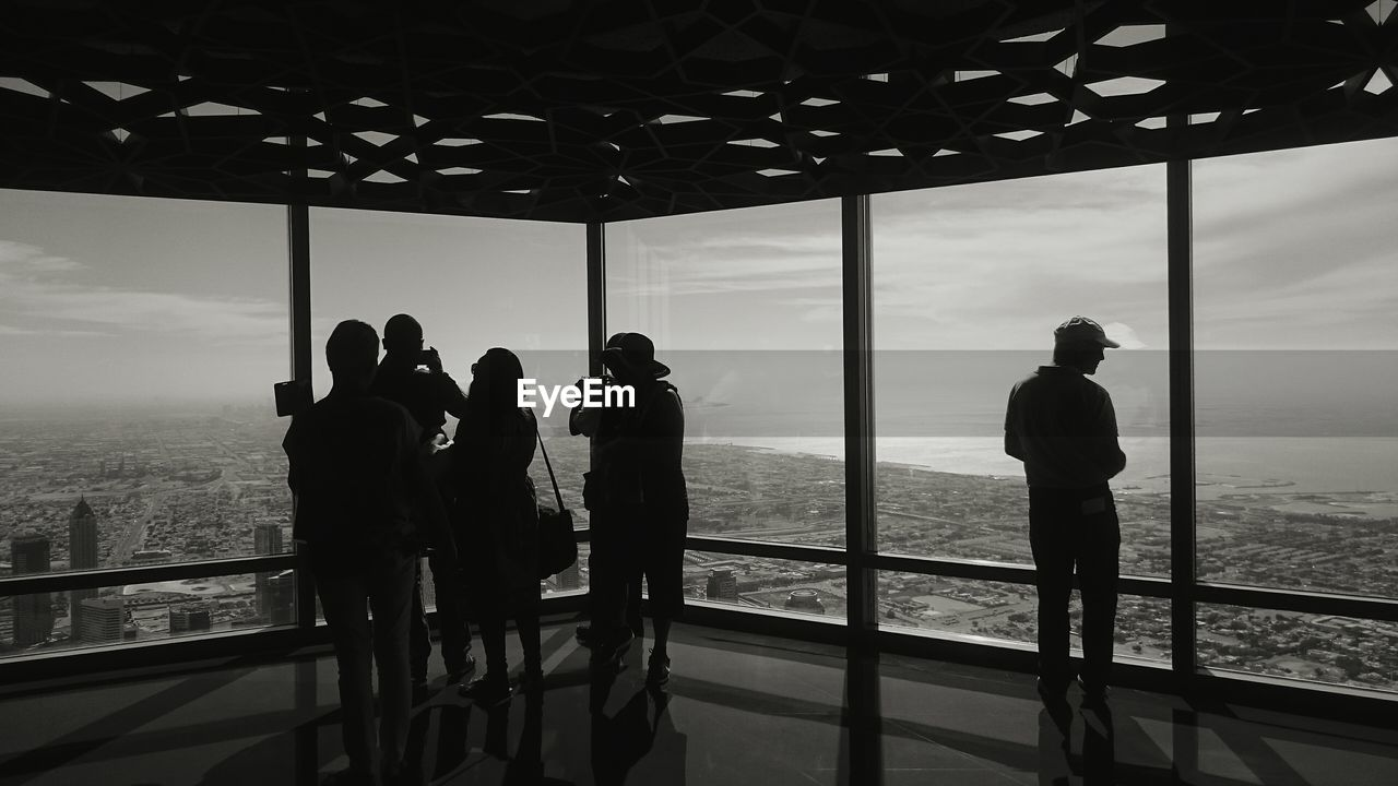 Silhouette People Looking Through Window From Burj Khalifa