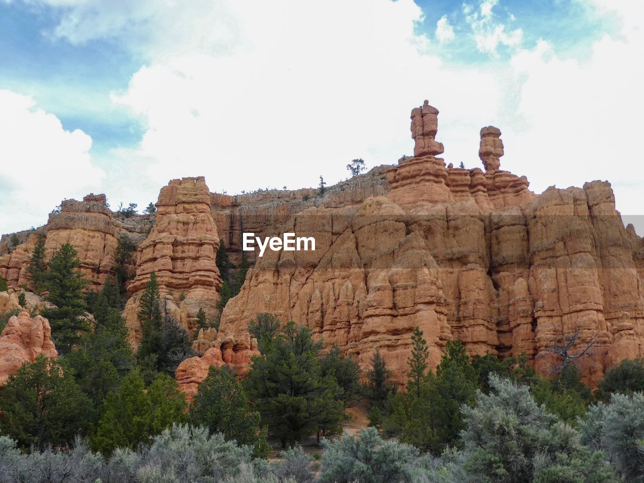 sky, plant, tree, travel, mountain, rock formation, travel destinations, nature, rock, day, solid, rock - object, low angle view, cloud - sky, tourism, beauty in nature, no people, scenics - nature, tranquility, tranquil scene, outdoors, eroded, formation