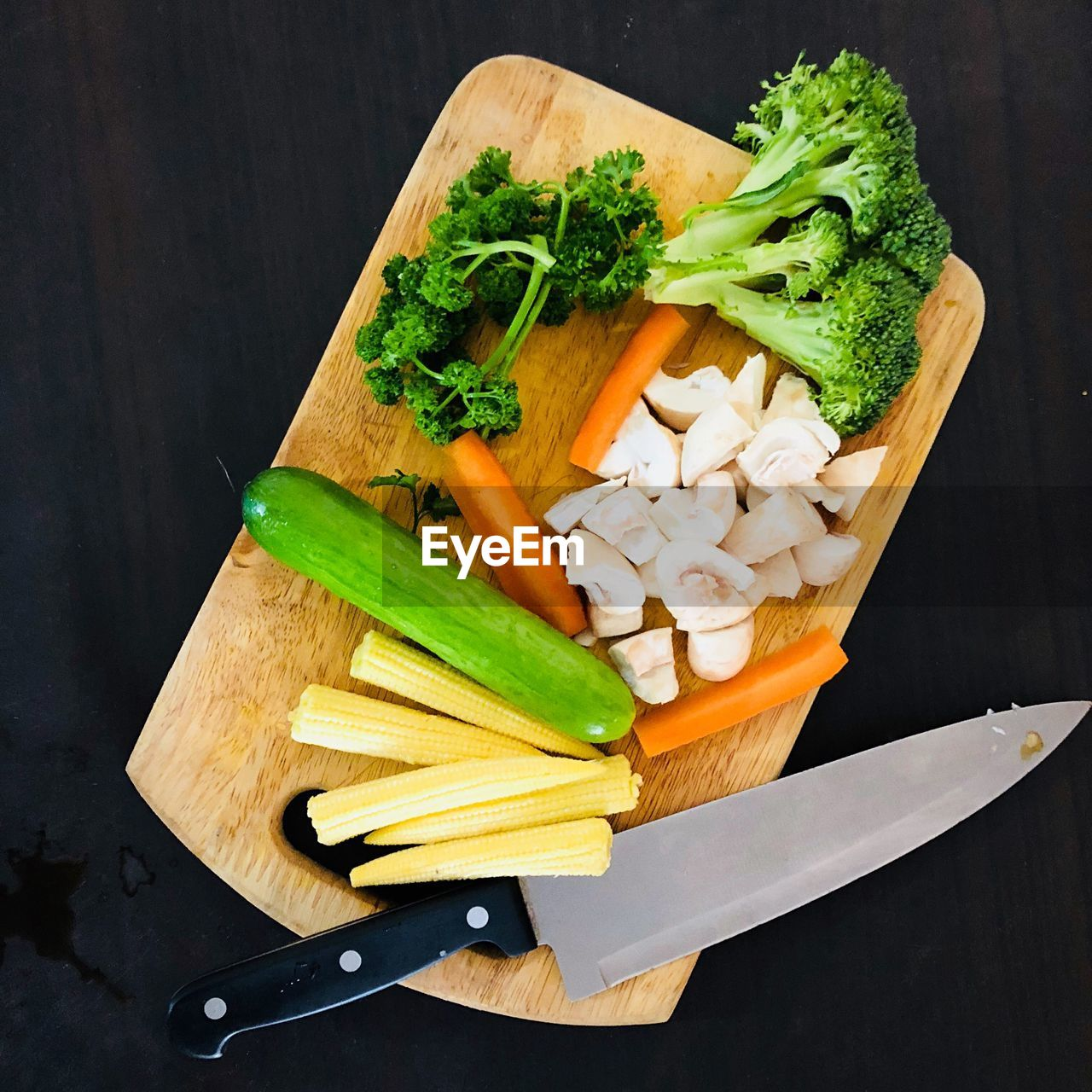High angle view of chopped vegetables with cutting board and knife on black background