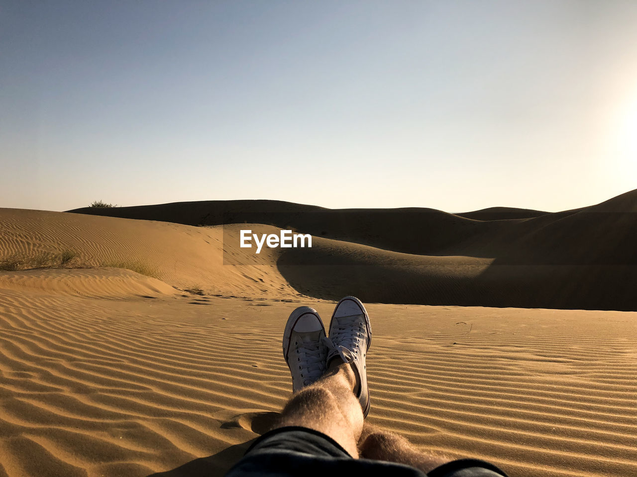 Low Section Of Man Resting On Sand At Desert