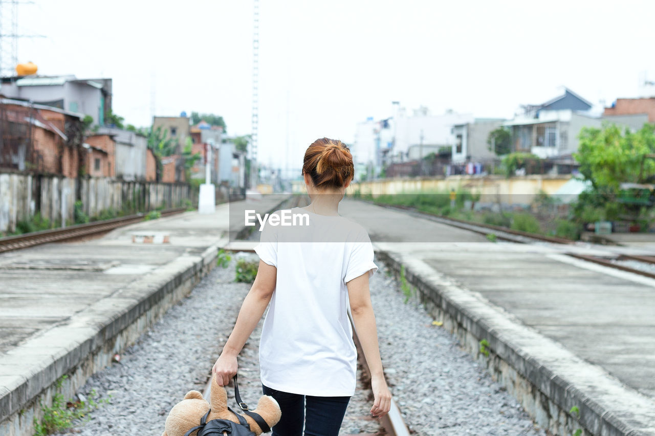 Rear View Of Holding Teddy Bear While Walking On Railroad Track