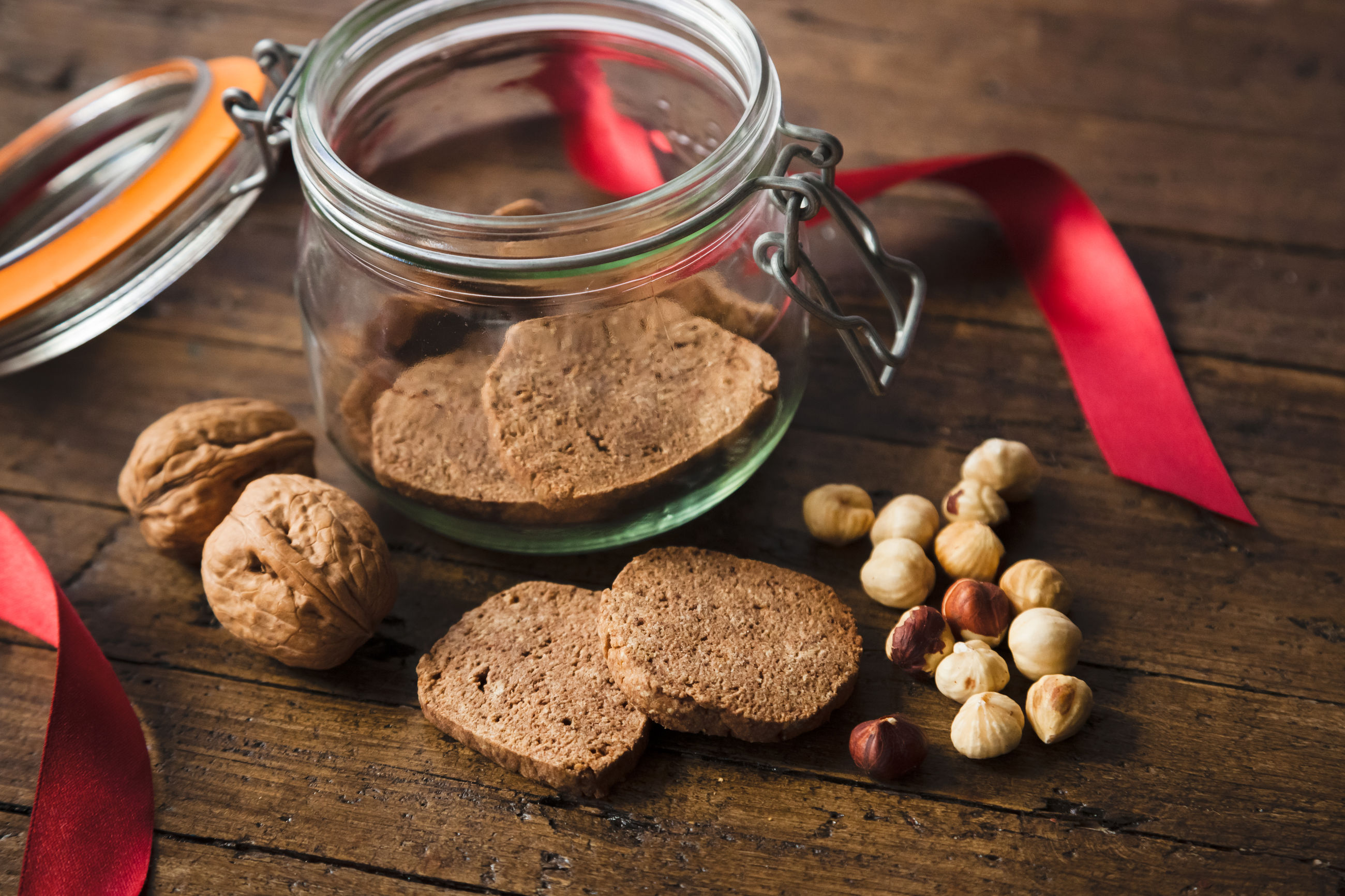 High angle view of cookies and walnuts by jar on table