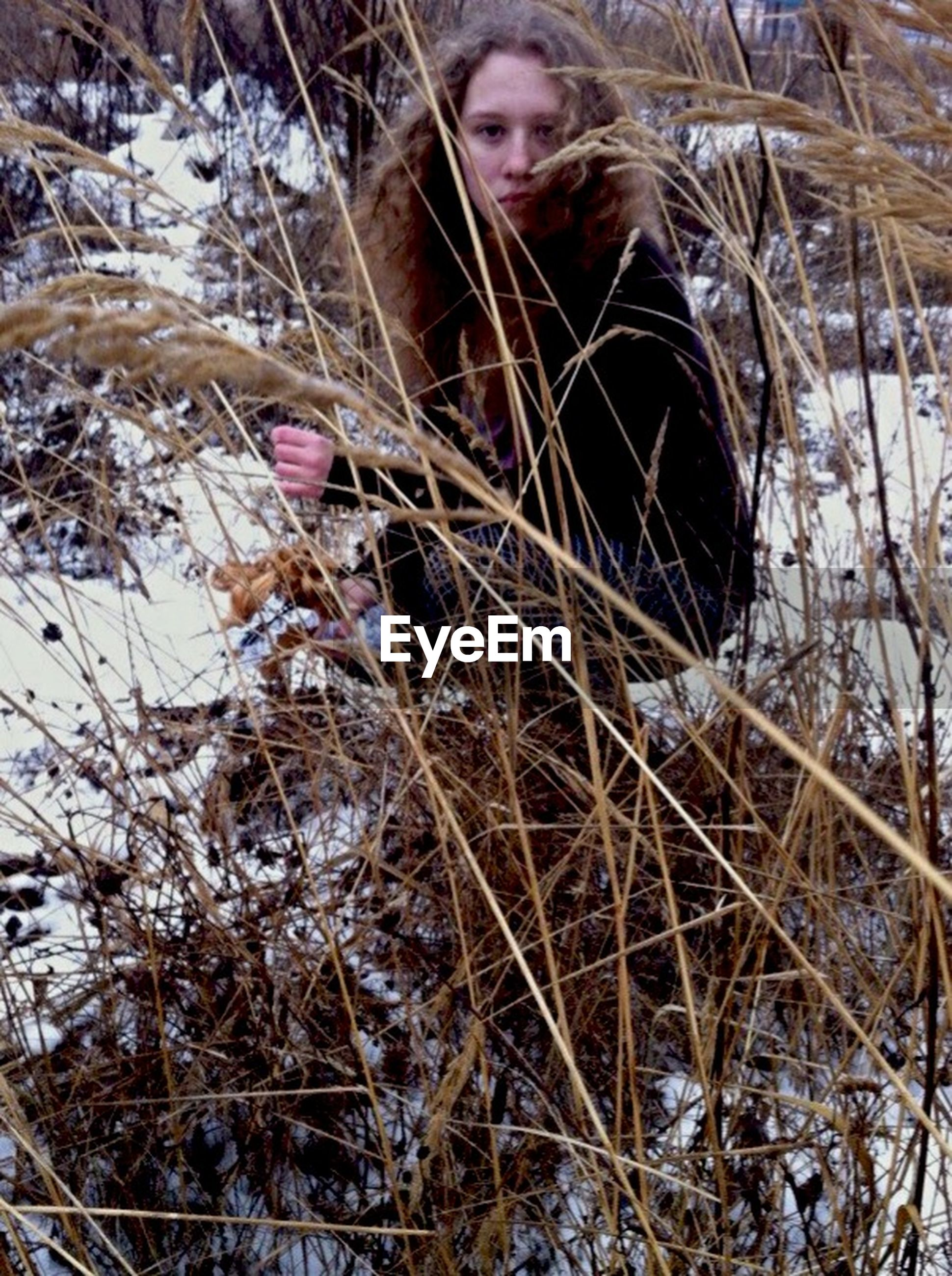 lifestyles, standing, leisure activity, front view, person, looking at camera, winter, cold temperature, dry, portrait, snow, plant, field, day, young adult, three quarter length, high angle view, outdoors