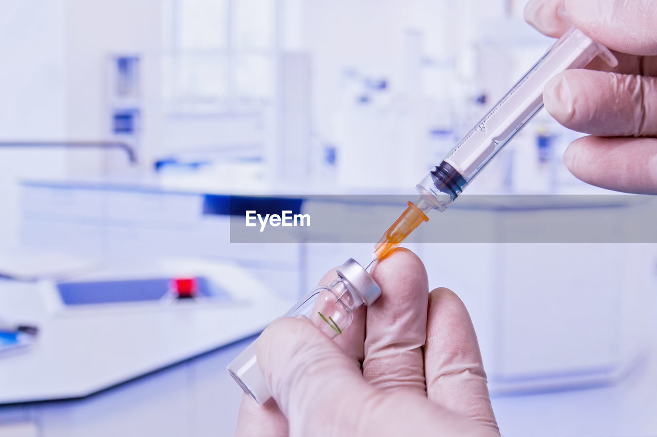 Cropped hand holding vial and syringe at hospital