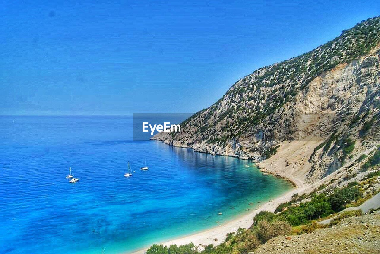 sea, blue, scenics, beauty in nature, water, nature, tranquil scene, tranquility, idyllic, no people, beach, outdoors, day, sky, mountain, clear sky, horizon over water, tree