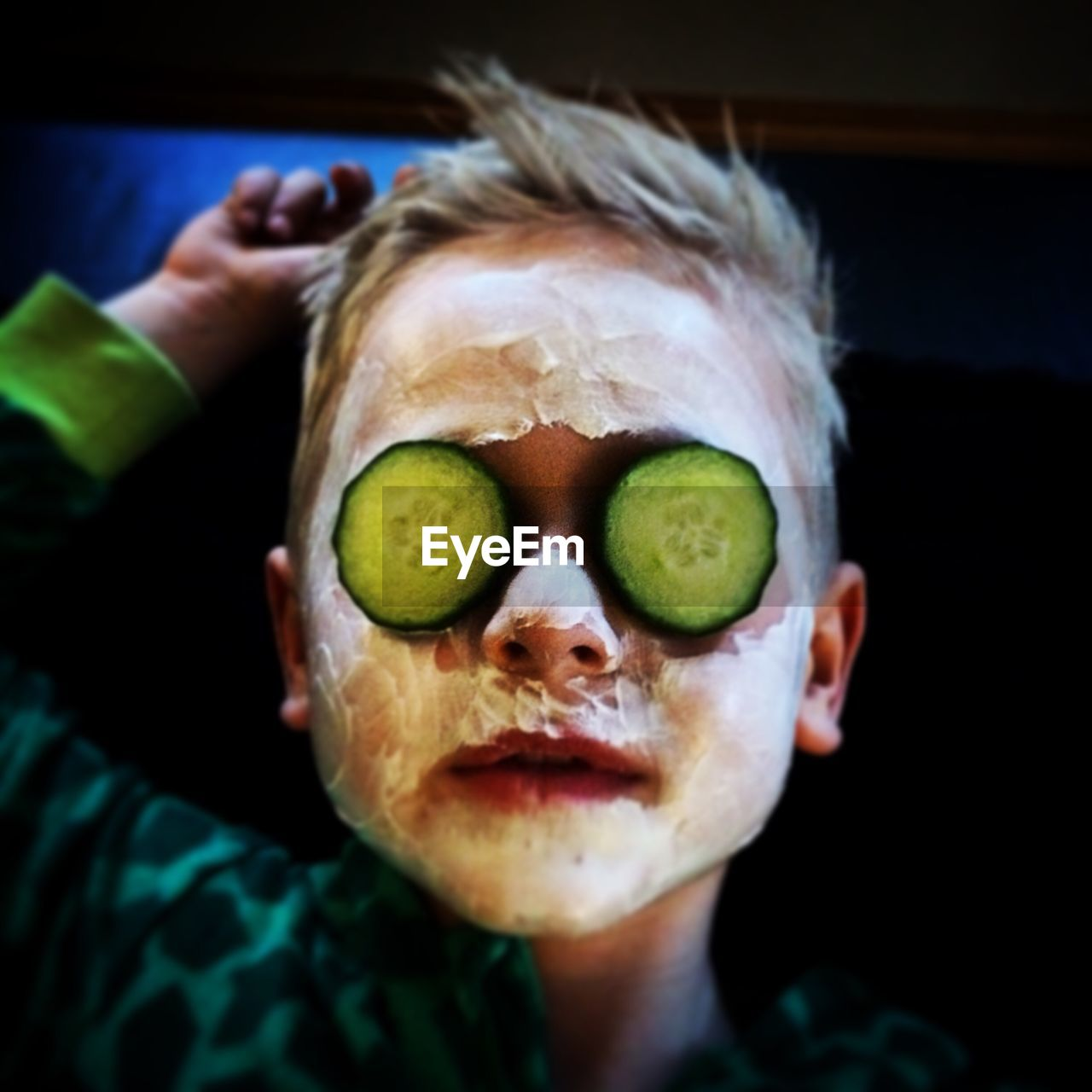 Close-up of boy wearing facial mask and cucumber slices on eyes
