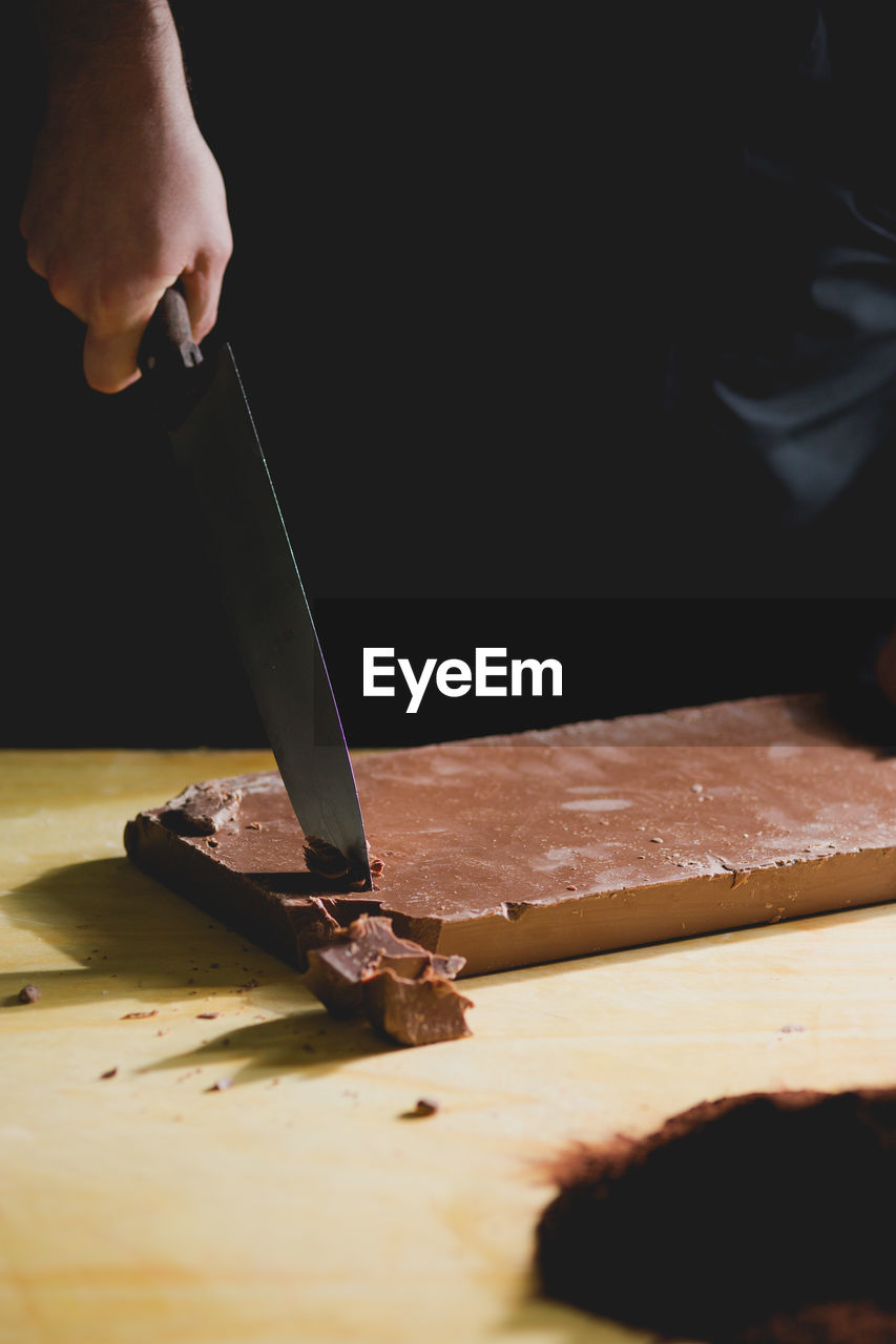 Midsection Of Man Holding Knife On Chocolate