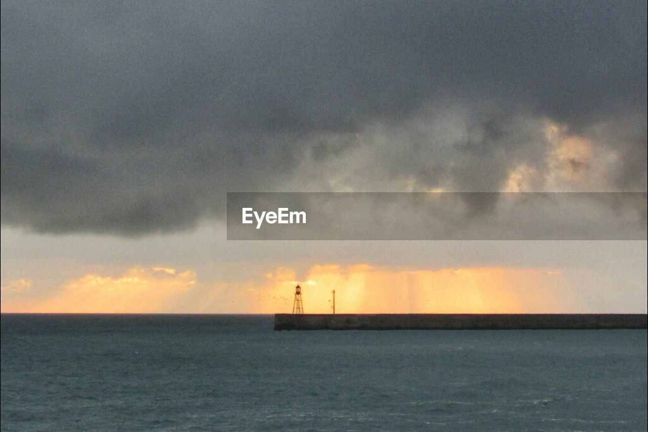 sea, sky, water, horizon over water, scenics, silhouette, tranquility, beauty in nature, cloud - sky, nature, waterfront, tranquil scene, outdoors, built structure, no people, lighthouse, sunset, day, nautical vessel, architecture, sailing, thunderstorm, offshore platform