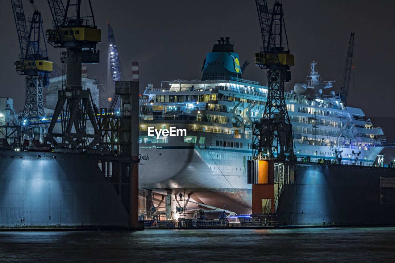 night, illuminated, architecture, built structure, building exterior, commercial dock, nautical vessel, harbor, transportation, industry, water, travel destinations, no people, outdoors, sky, sea, factory, shipyard, city