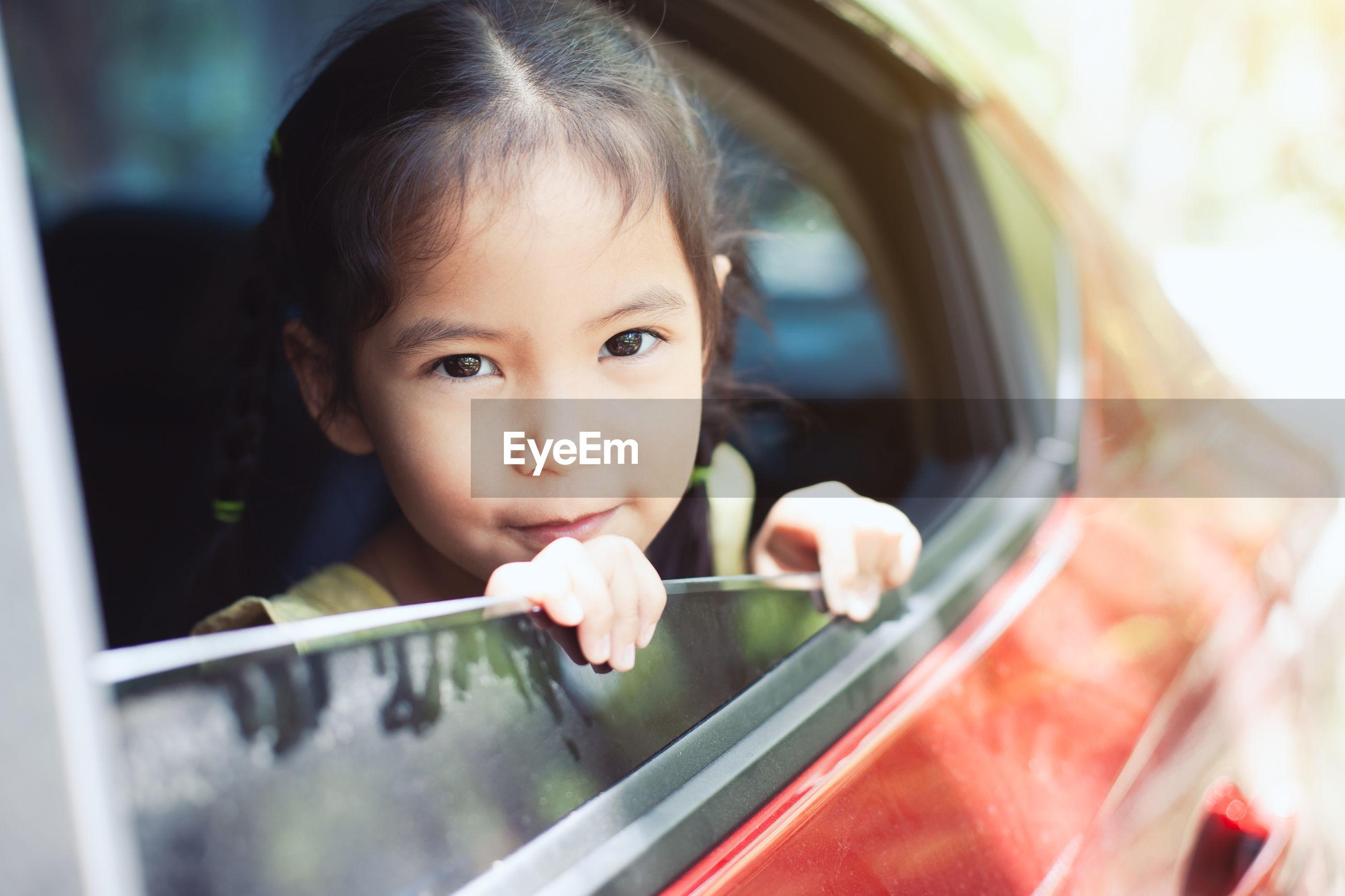 Portrait of cute girl looking through car window