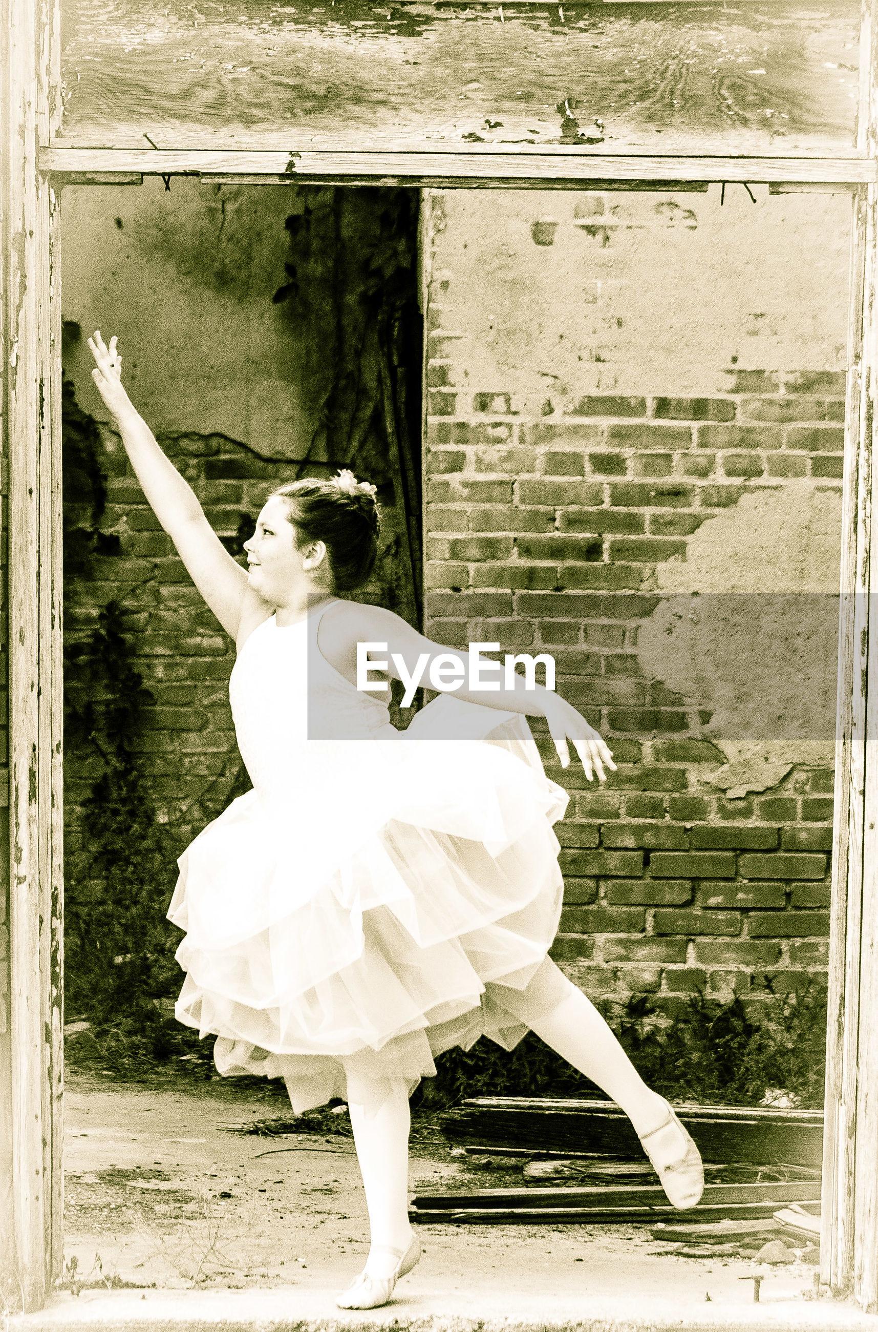 Ballet dancer dancing against brick wall