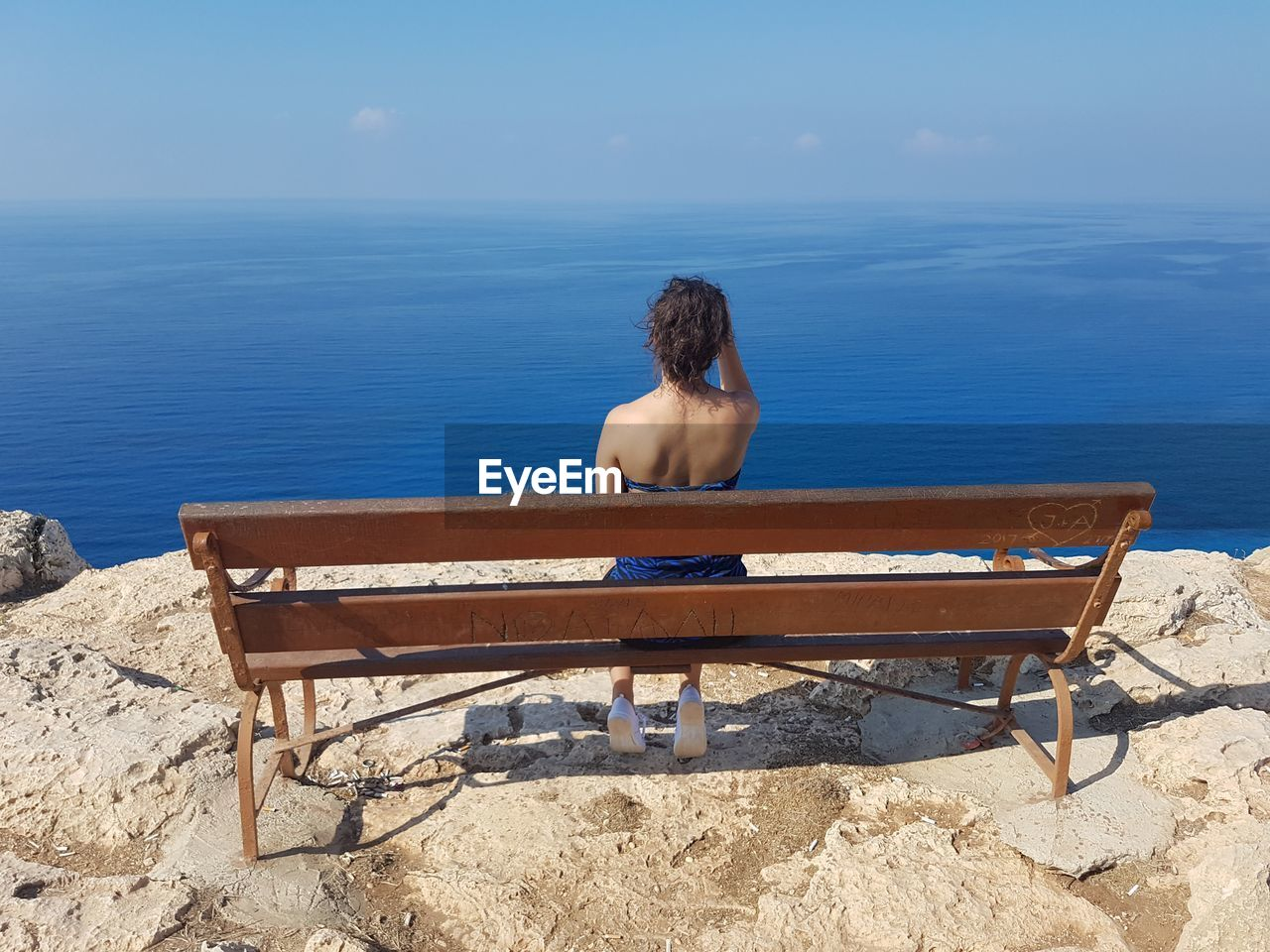 water, one person, rear view, sea, nature, sitting, land, real people, shirtless, relaxation, leisure activity, horizon, beach, horizon over water, sky, scenics - nature, tranquility, lifestyles, bench, outdoors, looking at view