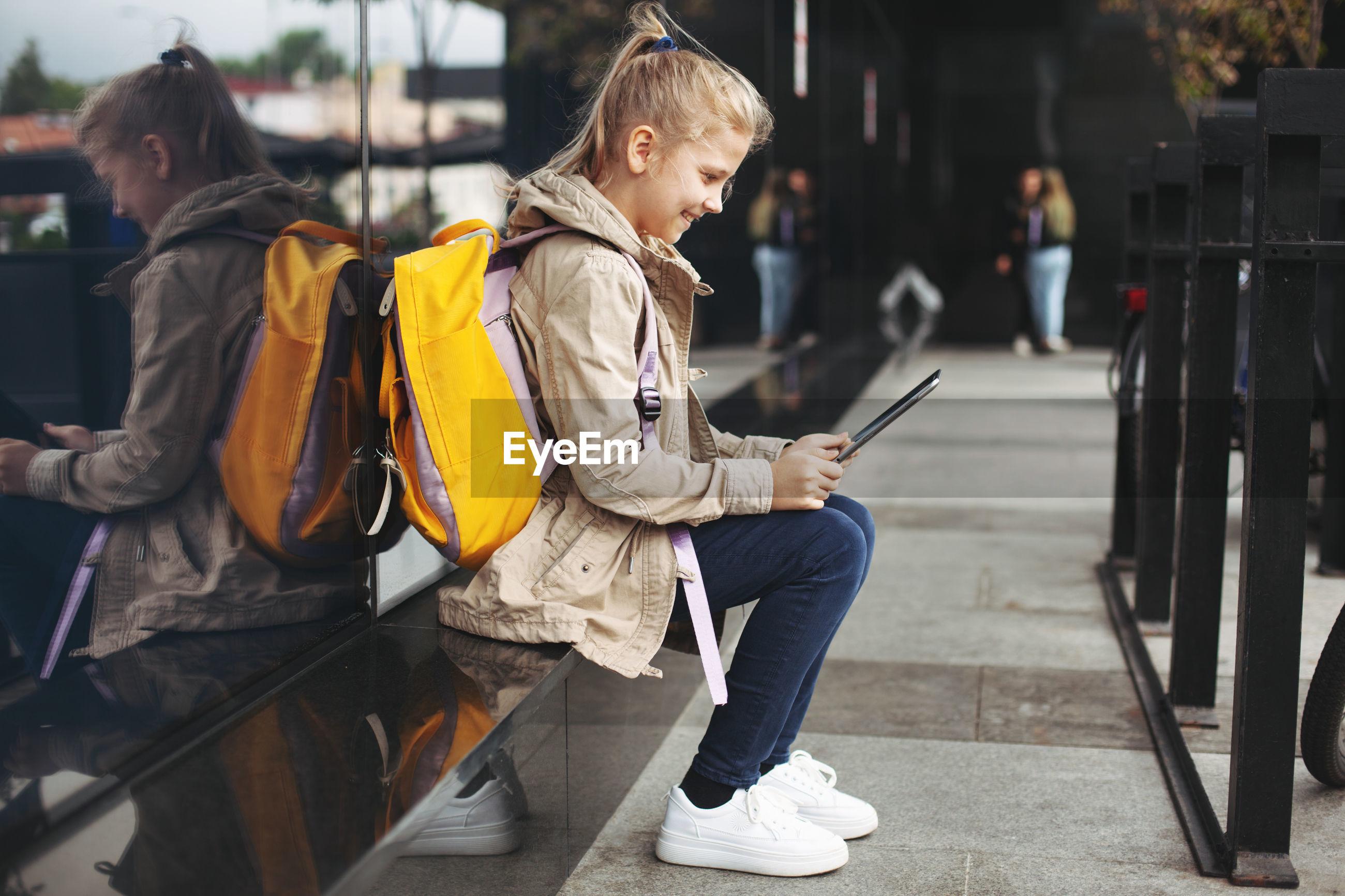 Girl using tablet in city
