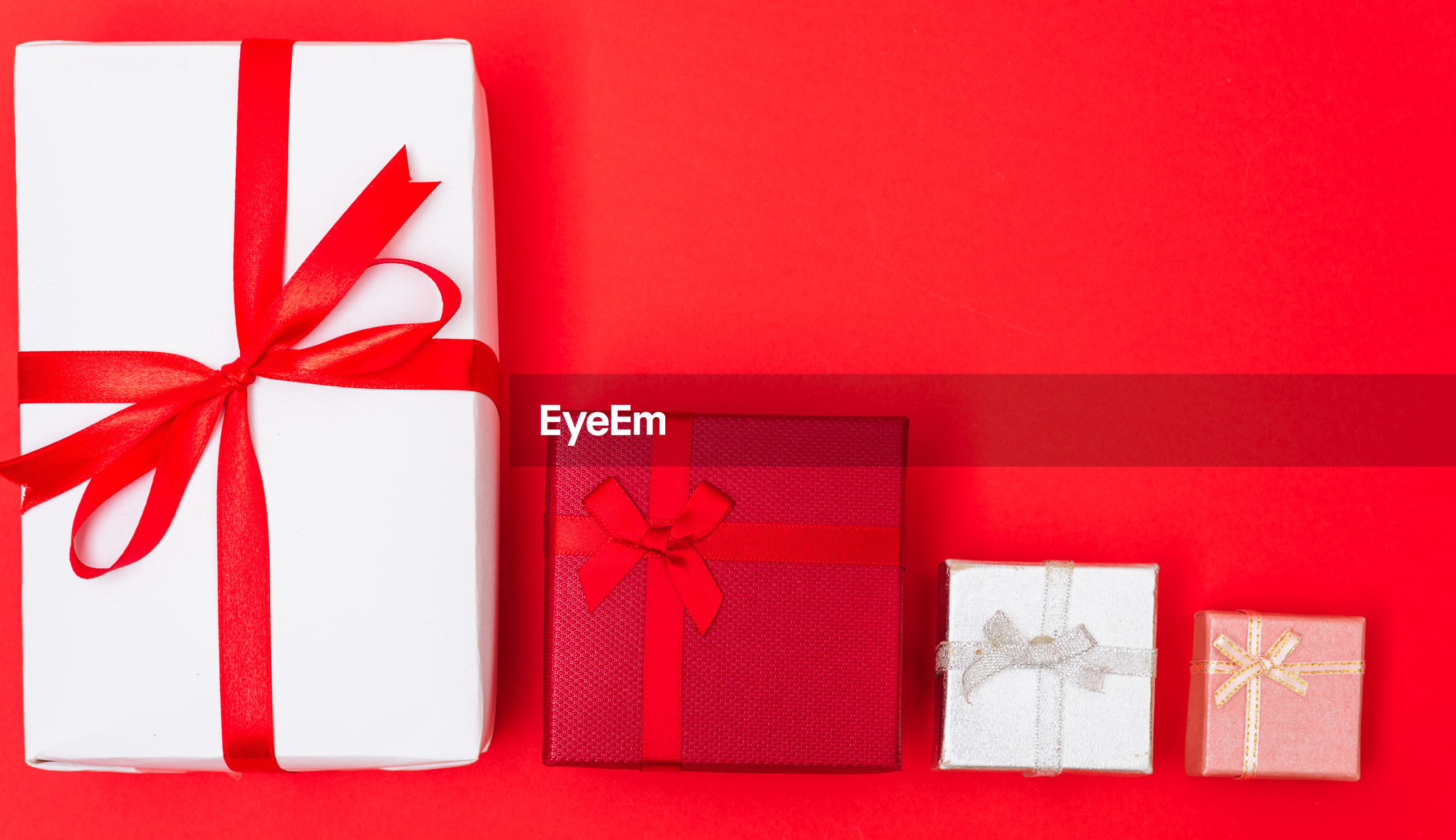 Directly above shot of gift boxes against red background