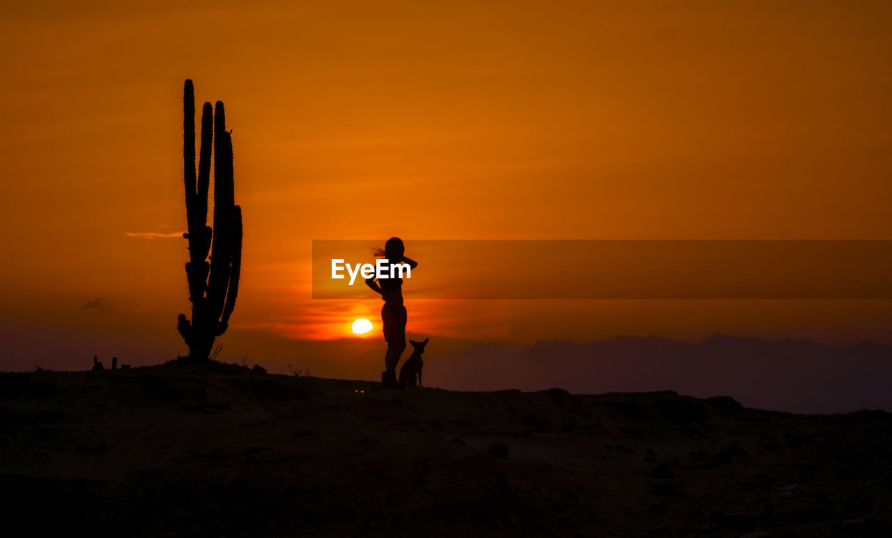 Silhouette woman standing with dog on field against orange sky during sunset