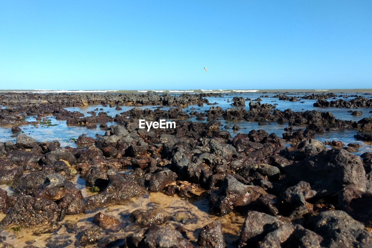 sky, rock, water, clear sky, rock - object, copy space, sea, solid, scenics - nature, nature, beauty in nature, tranquil scene, tranquility, beach, land, no people, day, horizon, blue, horizon over water, outdoors, rocky coastline