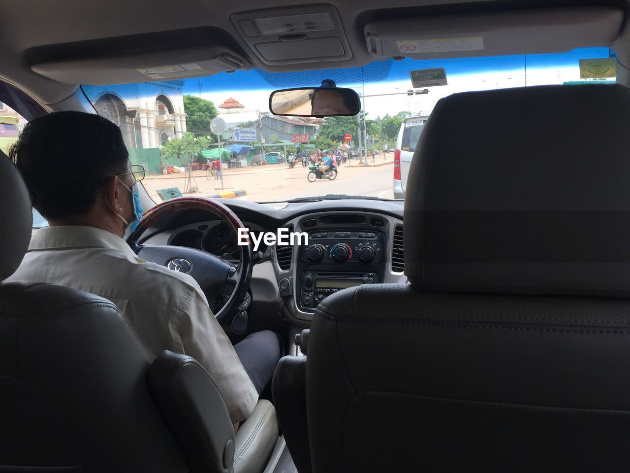 vehicle interior, transportation, car interior, car, land vehicle, mode of transport, rear view, vehicle seat, driving, real people, windshield, travel, men, sitting, dashboard, journey, steering wheel, day, car point of view, lifestyles, passenger seat, one person, sky, people