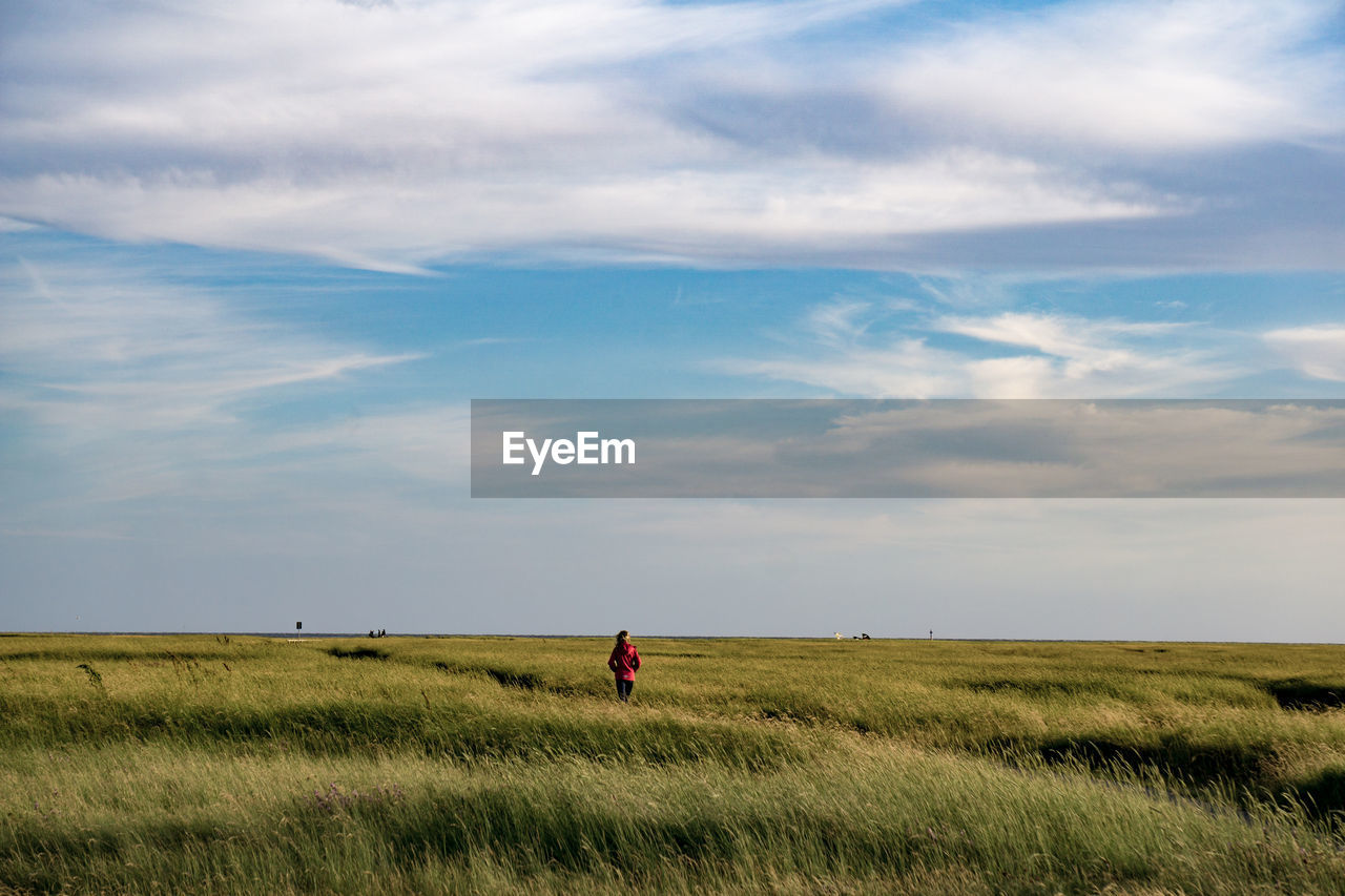 Rear View Of Woman On Grassy Field Against Sky