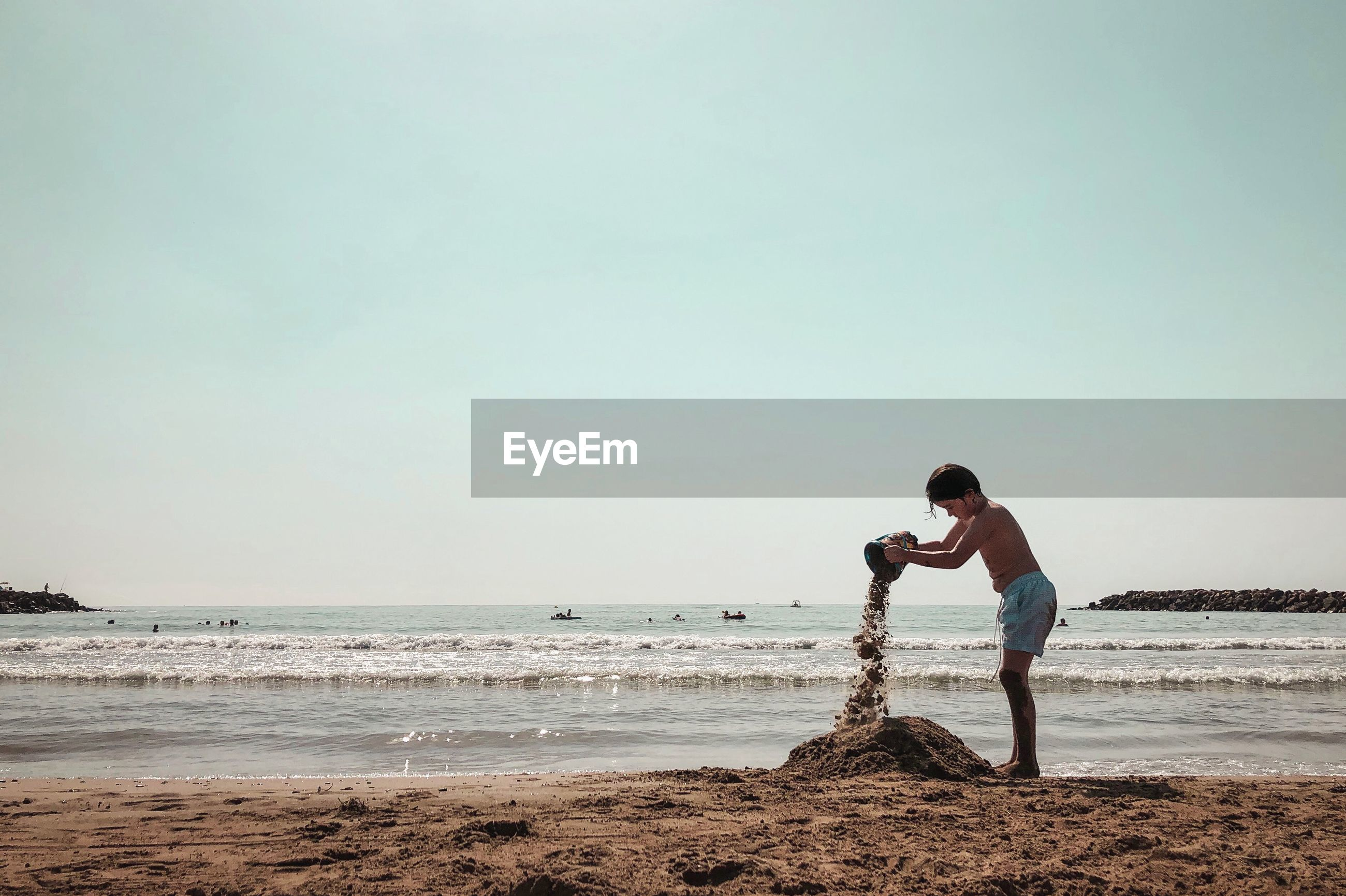 Full length of boy playing with sand while standing at beach against sky