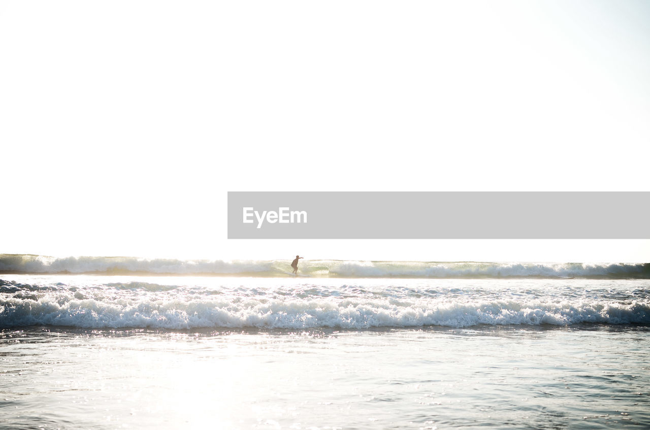 Distant view of person surfing against clear sky