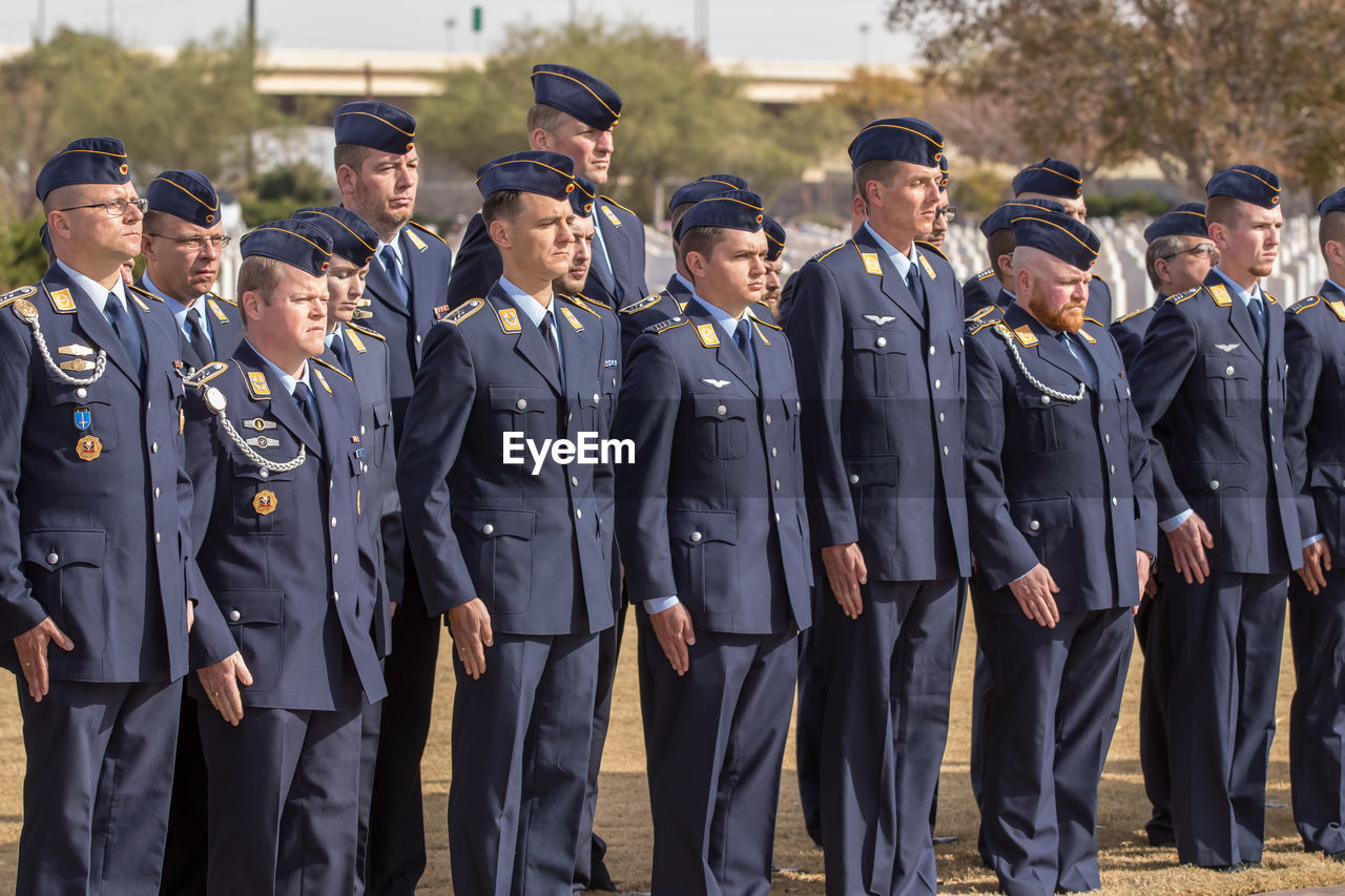 group of people, uniform, standing, men, clothing, day, large group of people, full length, law, adult, government, males, emotion, cooperation, young adult, crowd, teamwork, security, outdoors