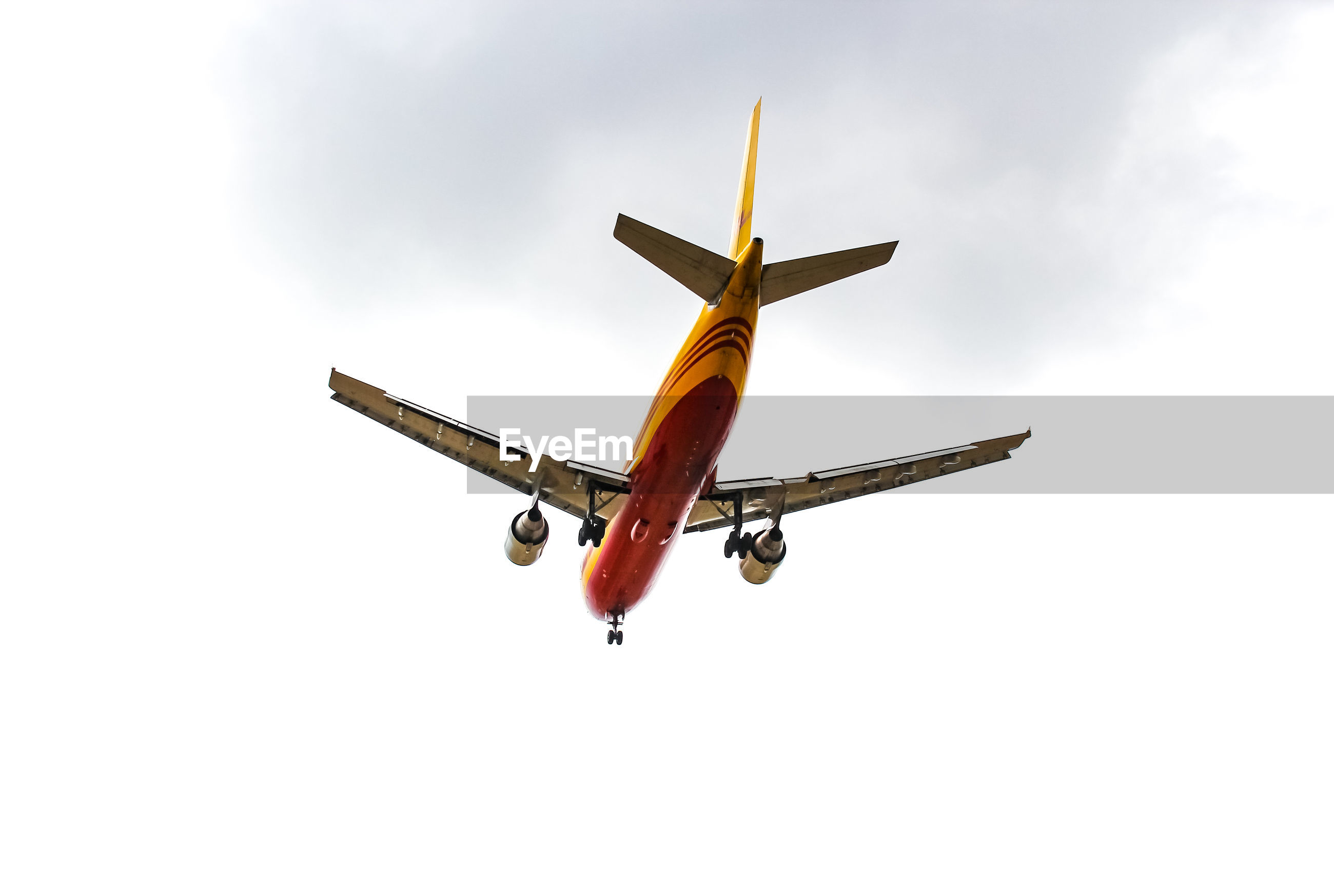 LOW ANGLE VIEW OF AIRPLANE IN MID-AIR AGAINST SKY