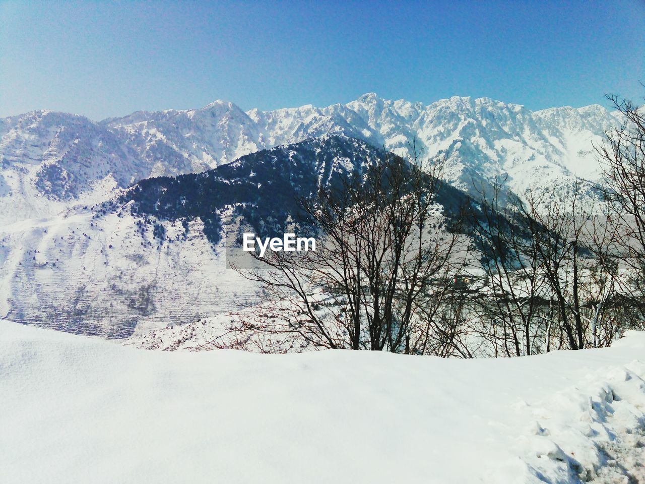 snow, winter, cold temperature, mountain, nature, weather, beauty in nature, tranquil scene, tranquility, frozen, scenics, white color, outdoors, landscape, cold, snowcapped mountain, no people, day, mountain range, blue, snowdrift, sky, bare tree, clear sky, tree