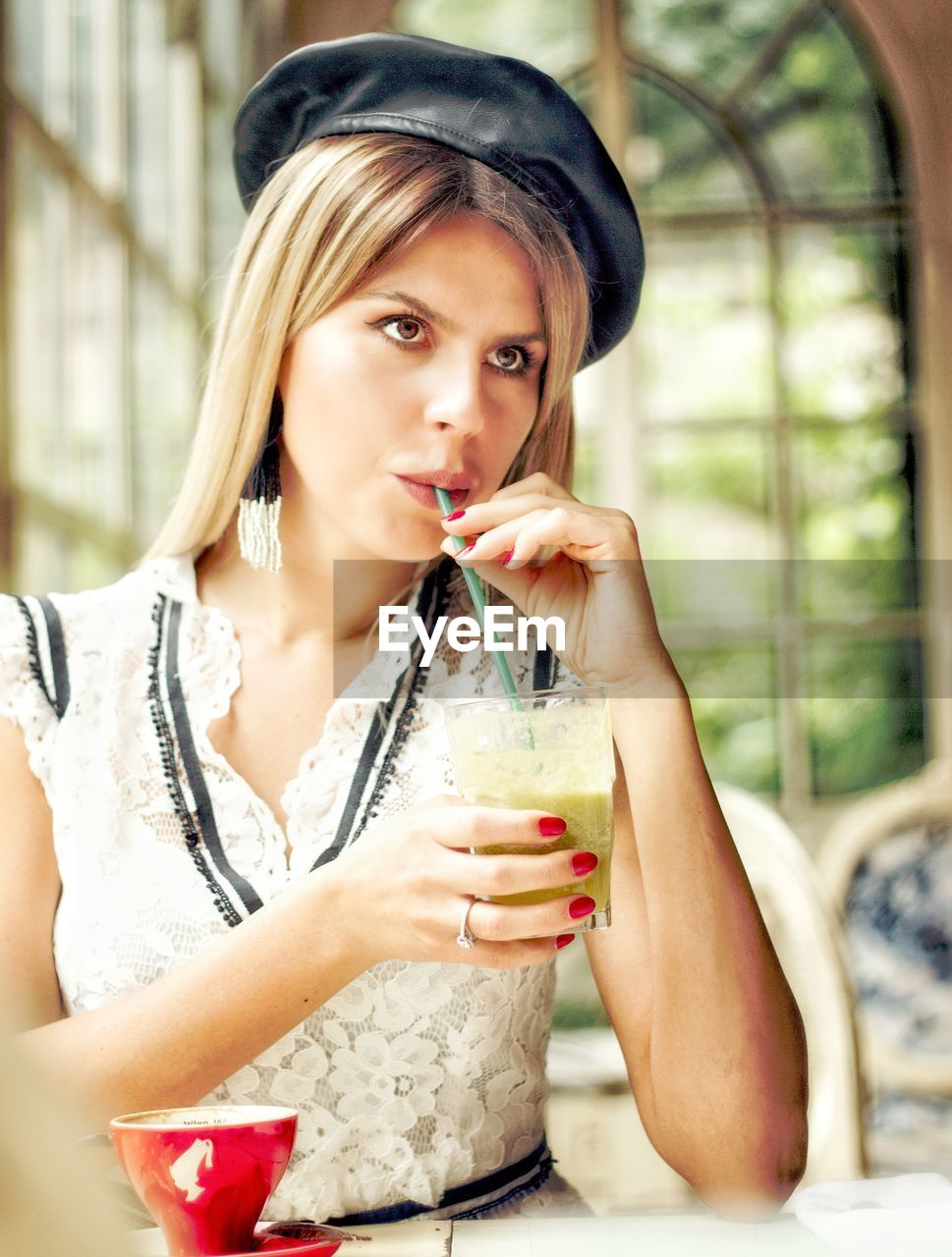 Beautiful woman looking away while drinking drink in cafe