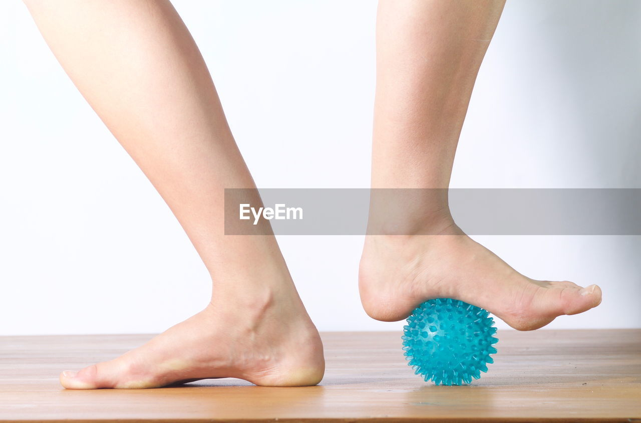 Low section of woman standing on rubber ball indoors