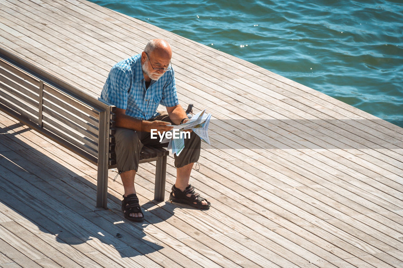 Full Length Of Man Reading Paper While Sitting By Lake On Bench During Sunny Day