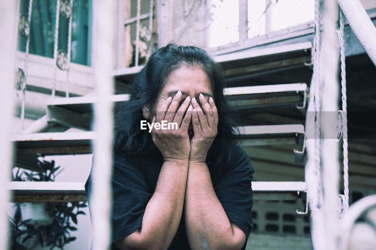 one person, real people, front view, hand, lifestyles, obscured face, covering, emotion, portrait, sadness, unrecognizable person, human body part, head in hands, hiding, young adult, adult, headshot, human hand, human face, depression - sadness, depression, hands covering eyes