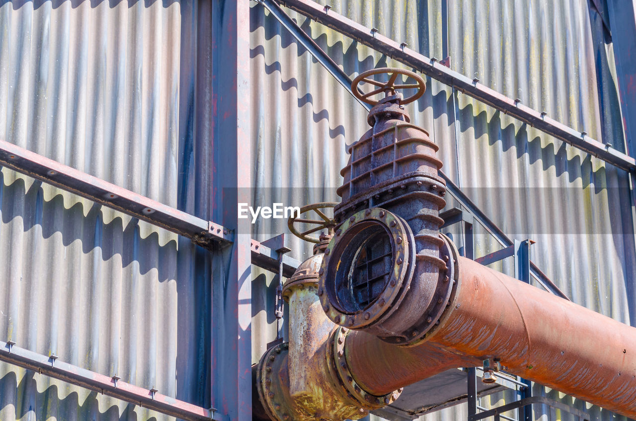 Low angle view of pipe attached to corrugated iron on factory
