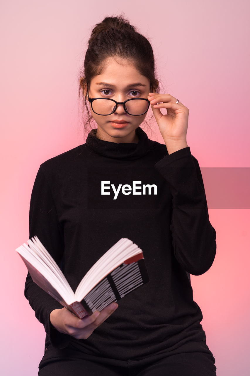studio shot, indoors, front view, one person, colored background, holding, glasses, looking at camera, standing, eyeglasses, portrait, casual clothing, waist up, lifestyles, child, pink background, three quarter length, cut out, innocence, hairstyle, pre-adolescent child