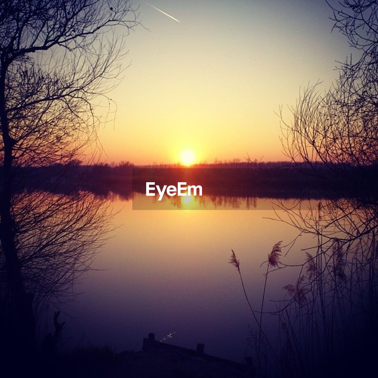 sunset, beauty in nature, reflection, water, nature, tranquil scene, scenics, tranquility, silhouette, sun, sky, lake, idyllic, no people, outdoors, tree, travel destinations, sunlight, bare tree, clear sky, day