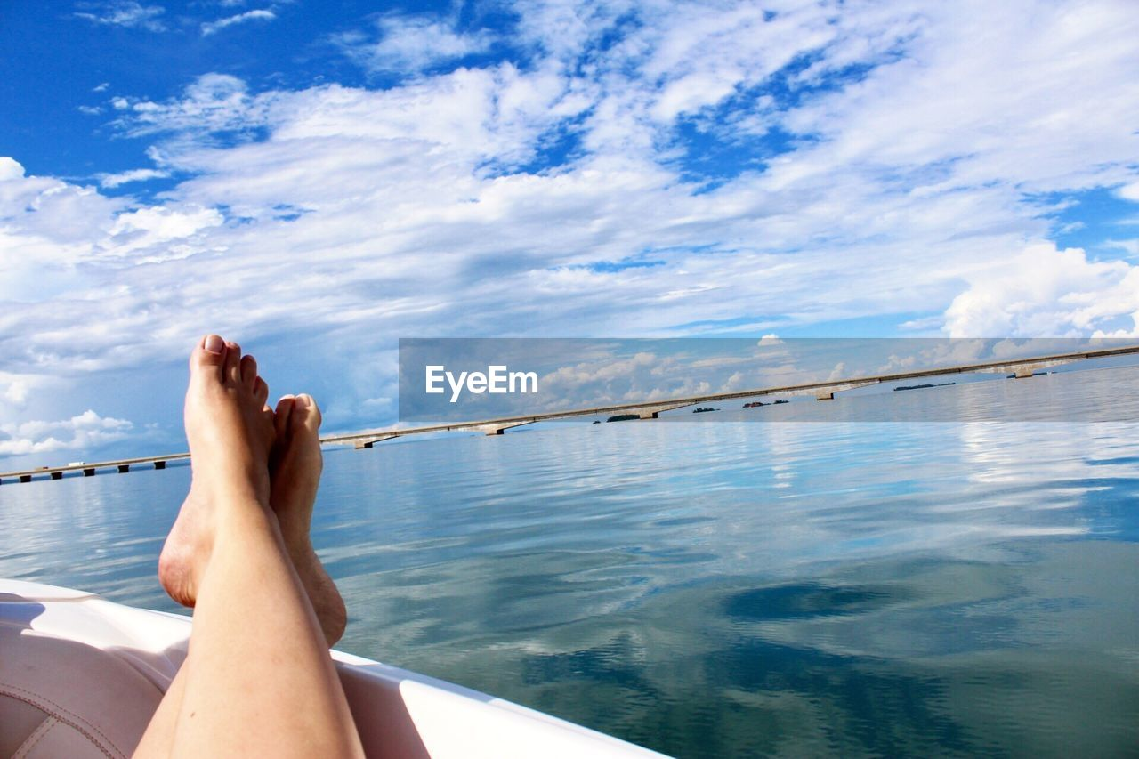 Low Section Of Woman Relaxing In Boat On Sea Against Cloudy Sky