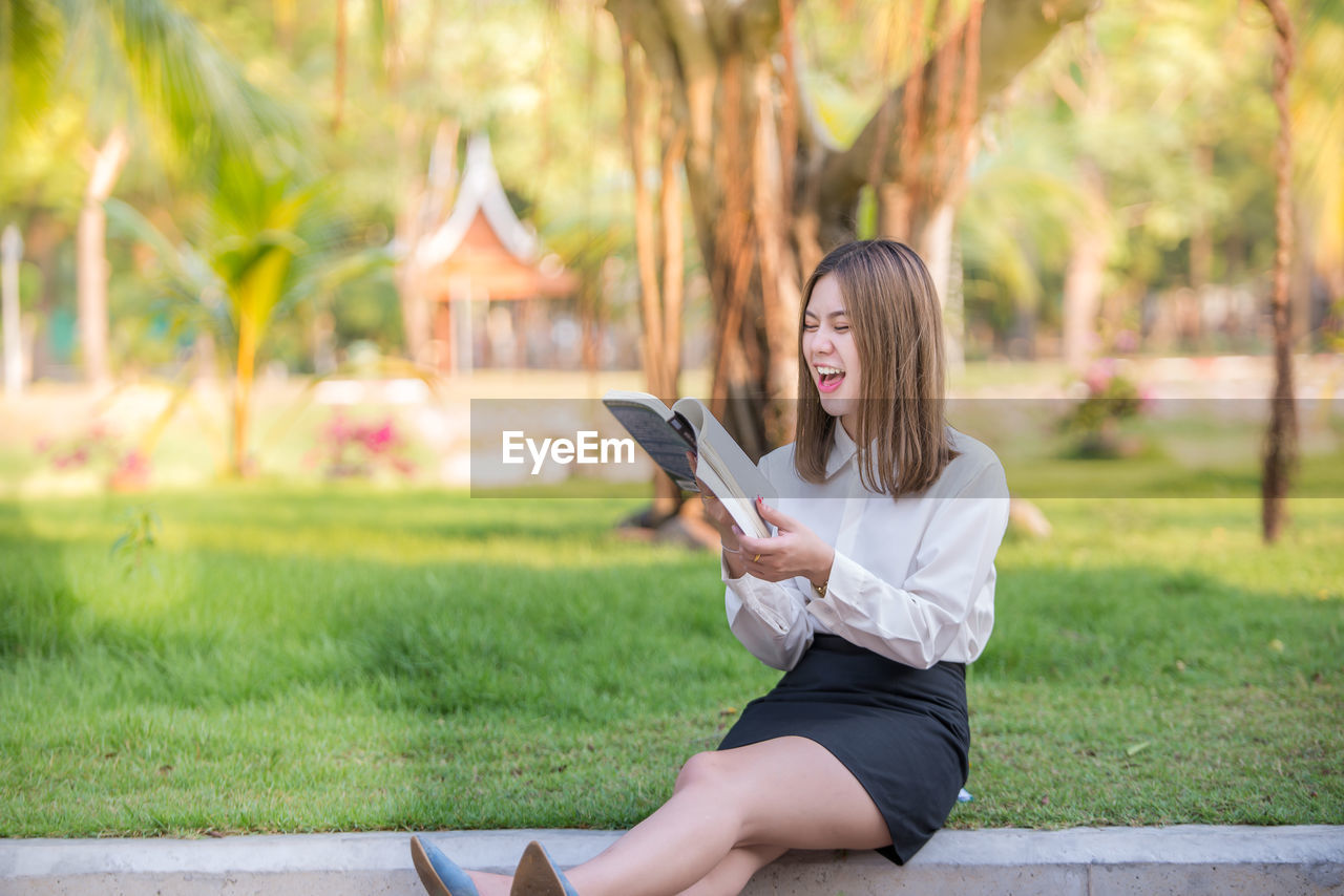 Happy businesswoman reading book while sitting at park