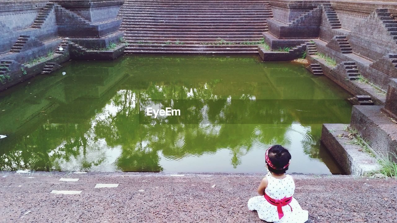 Rear View Of Girl Sitting In Front Of Pond