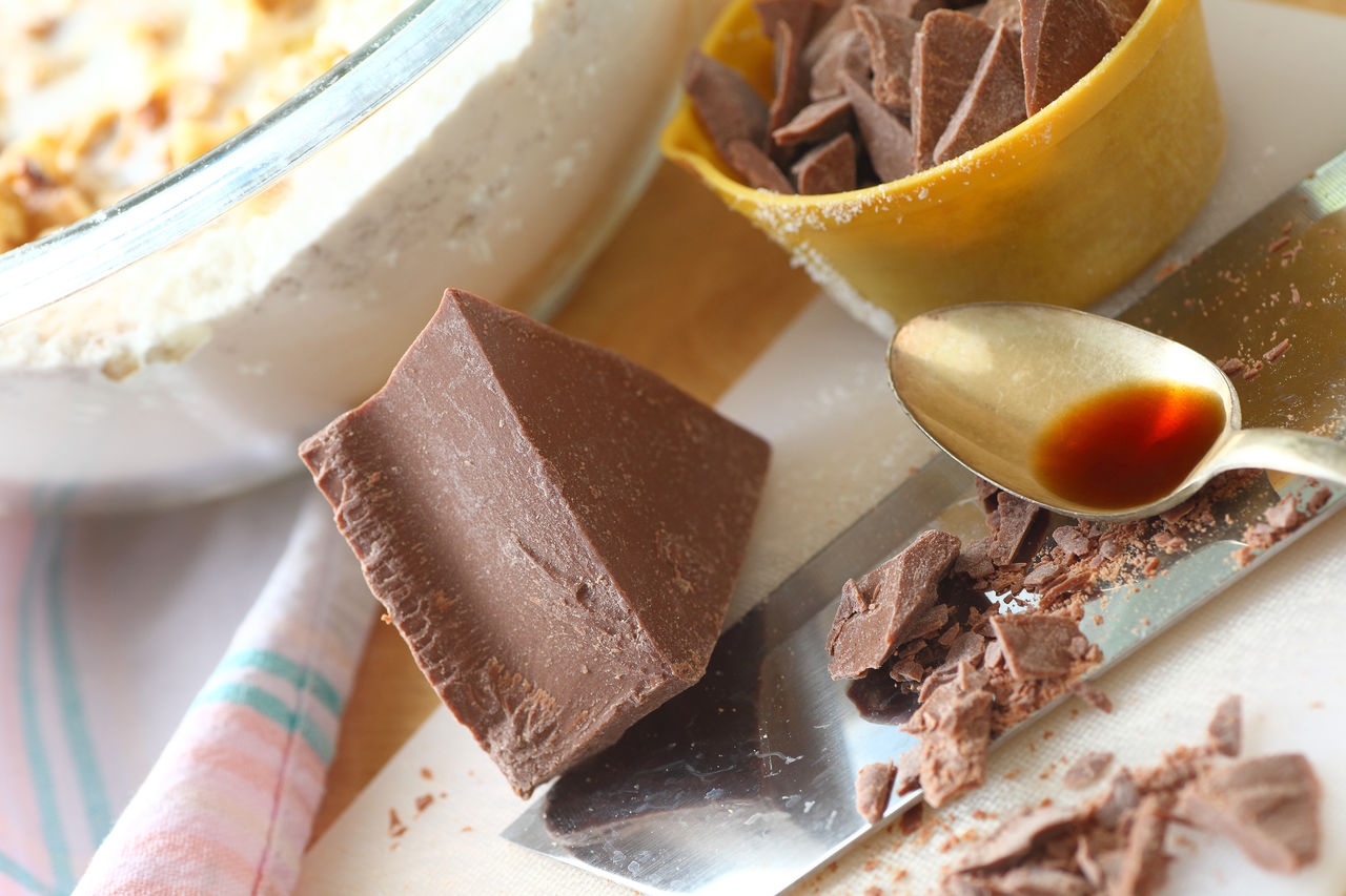 Tilt image of chopped chocolate and vanilla syrup in spoon on table