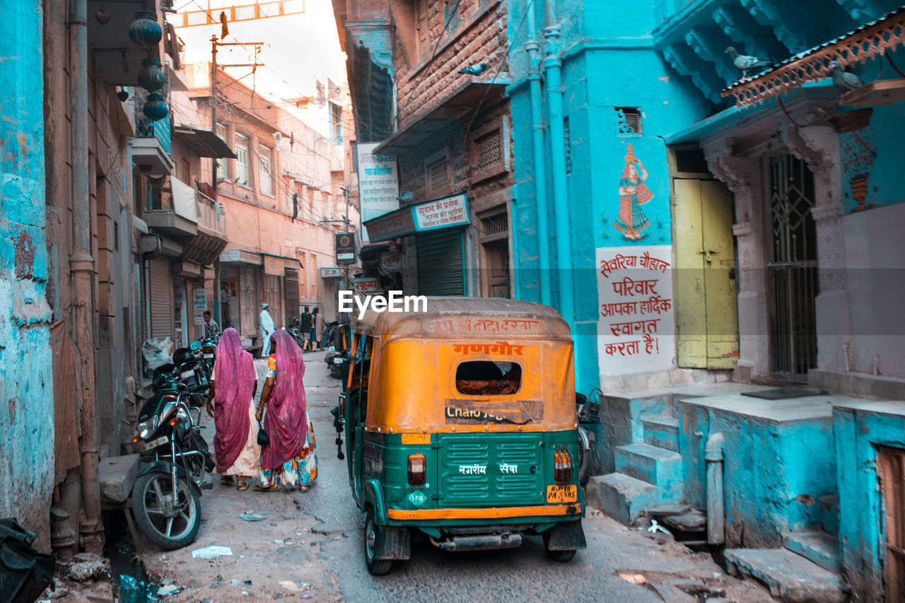 architecture, building exterior, mode of transportation, city, built structure, transportation, land vehicle, street, day, building, rickshaw, public transportation, outdoors, travel, incidental people, motor vehicle, road, city life, residential district, people