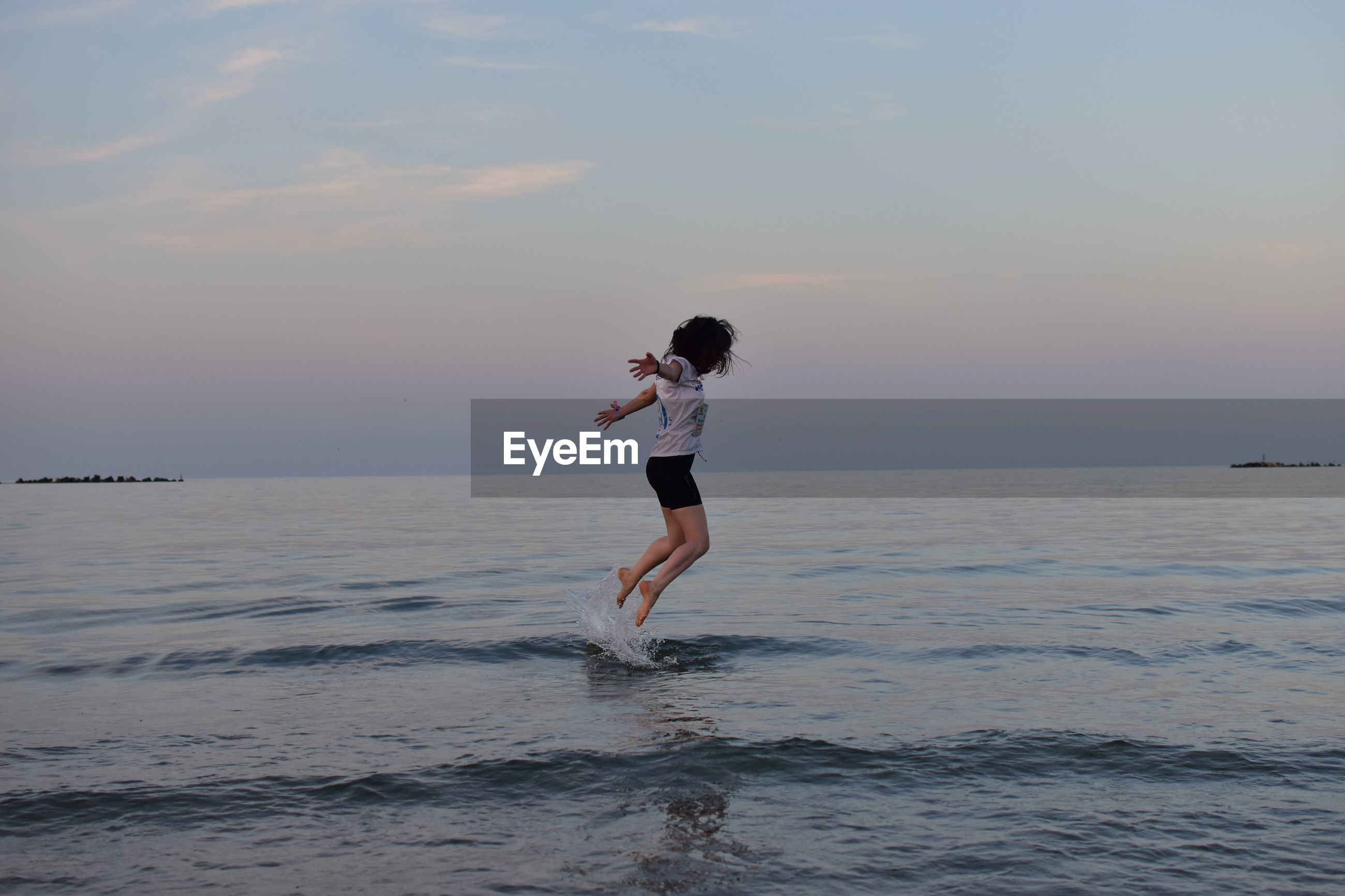 Side view of young woman jumping in sea against sky at sunset