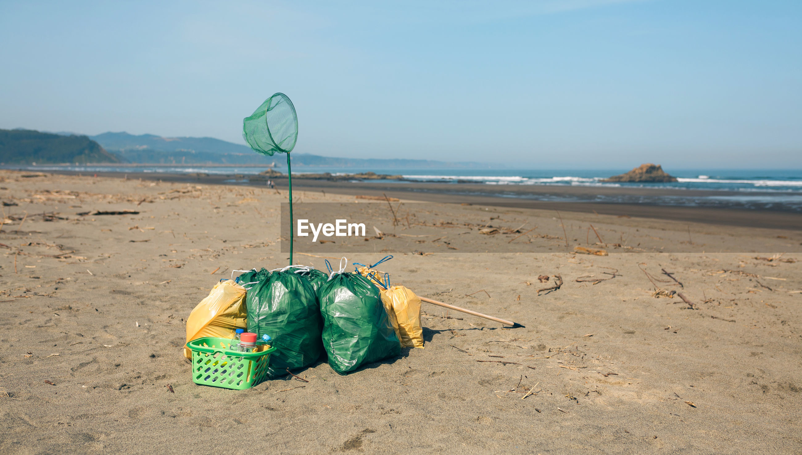 GREEN CONTAINER ON BEACH AGAINST SEA