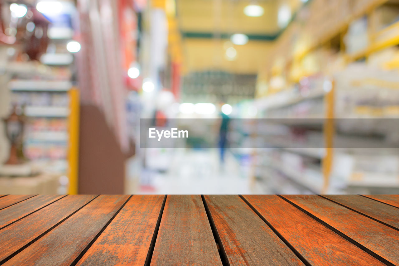 focus on foreground, wood - material, indoors, no people, in a row, architecture, illuminated, empty, building, close-up, glass - material, table, flooring, built structure, pattern, arrangement, store, large group of objects, seat