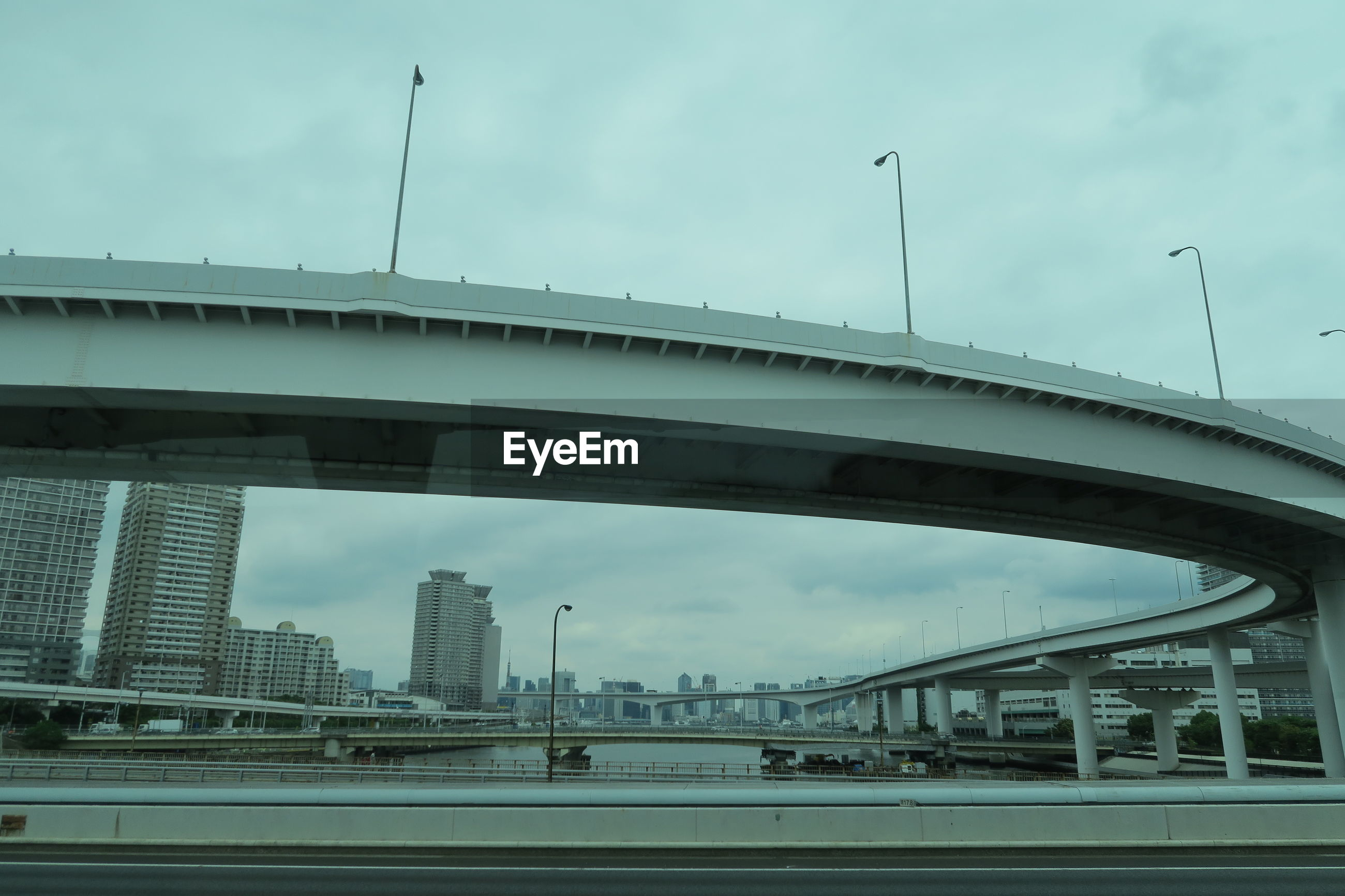 LOW ANGLE VIEW OF ELEVATED ROAD AGAINST CLOUDY SKY