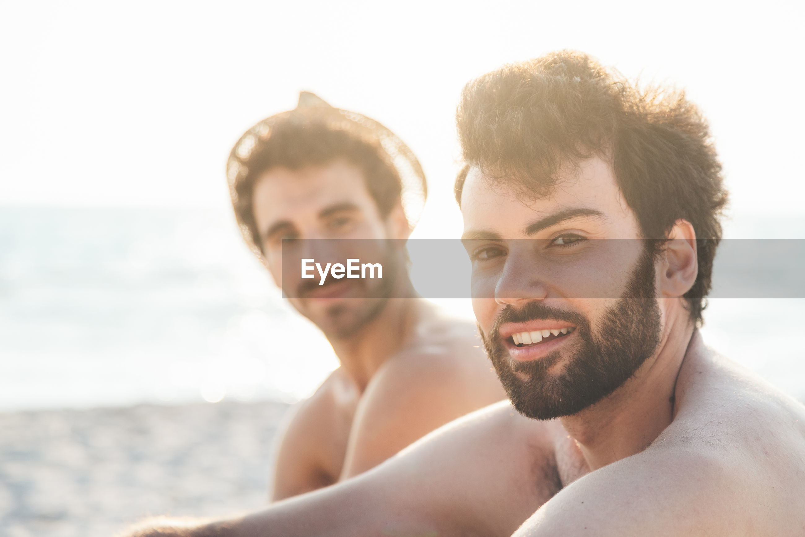 Portrait of handsome young men sitting at beach