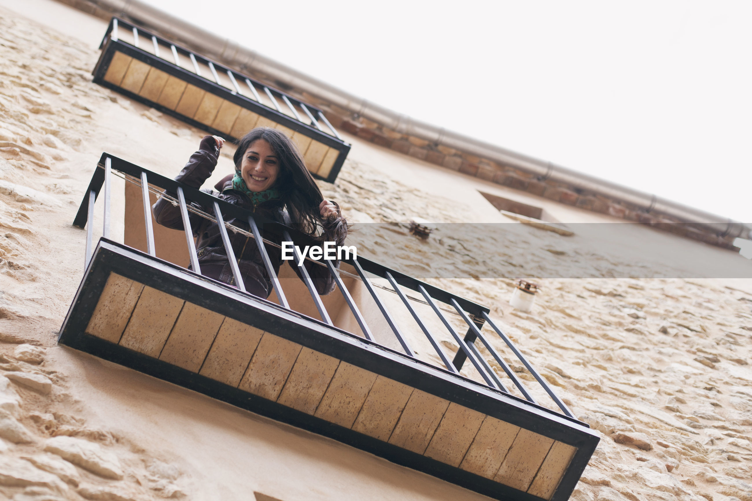 Low angle portrait of mid adult woman standing balcony