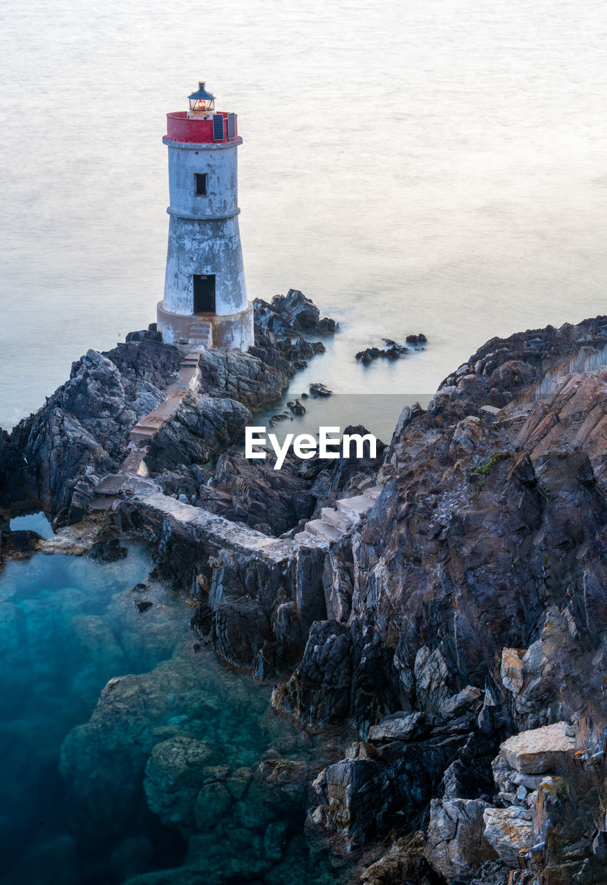 High angle view of lighthouse on rock formation by sea