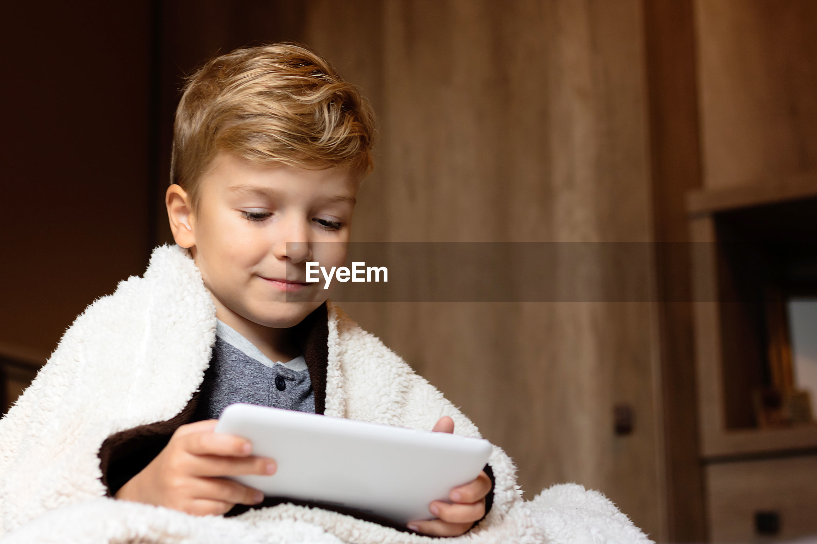 CUTE BOY USING MOBILE PHONE IN LAPTOP